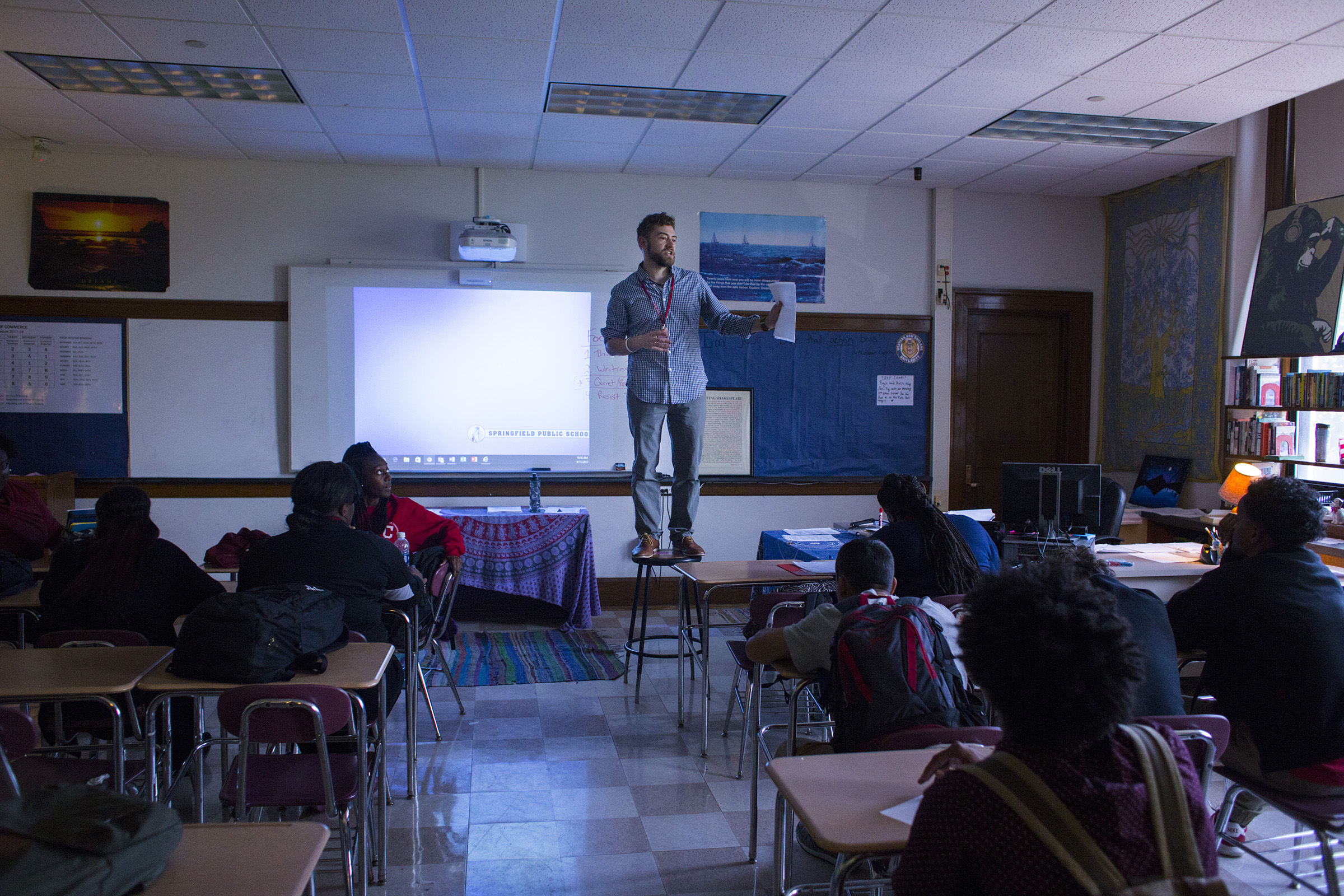Brian Damboise, an English and journalism teacher at the High School of Commerce, stands on a stool in order to get the attention of his students at the beginning of their class in Springfield, Mass., on Monday, September, 11, 2017. (Photo by Brittany Greeson)