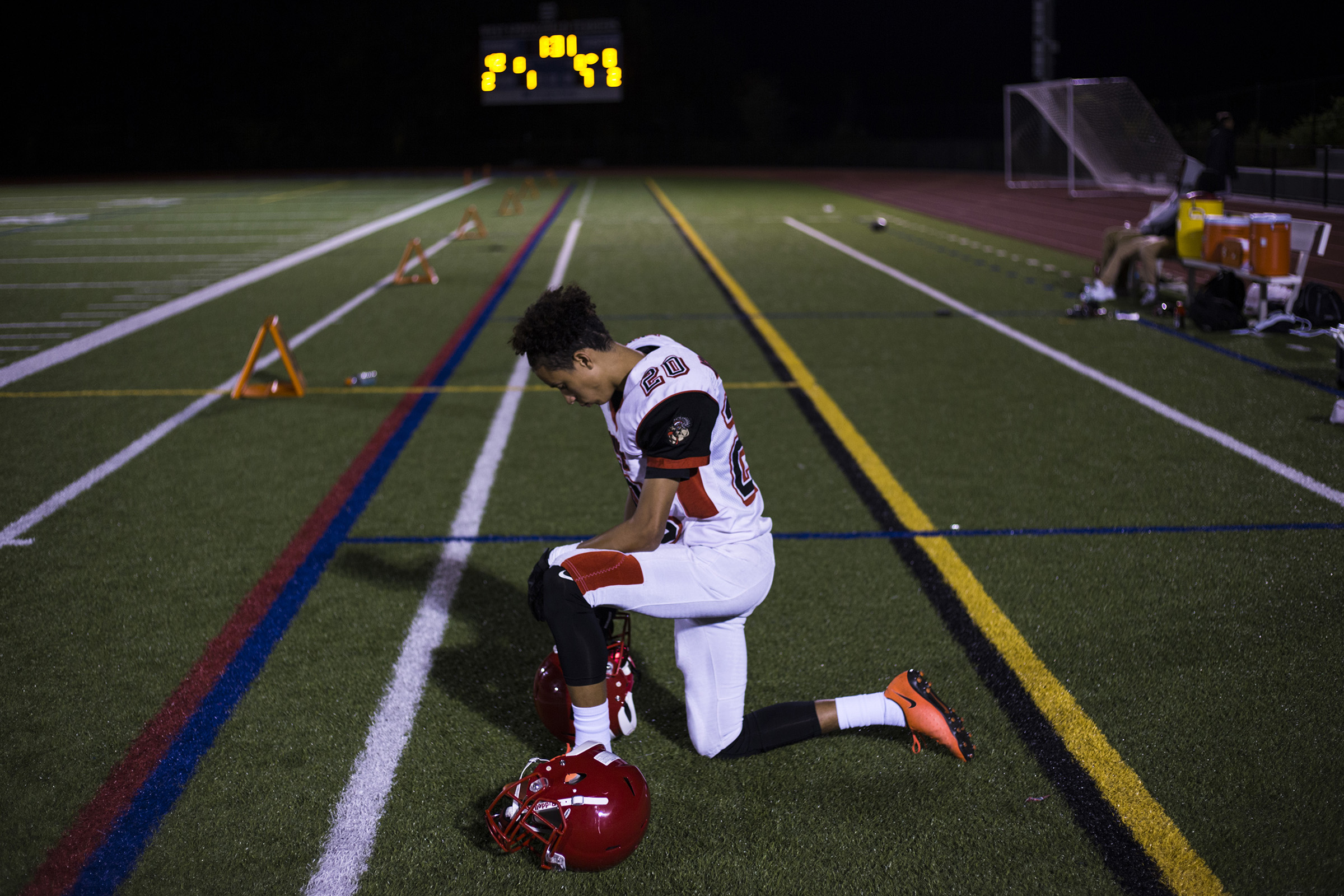 Wide receiver, David Porche Mayes, of the High School of Commerce kneels as he waits for the clock to run out as his team faces a 0-42 half-time score during a game in West Springfield, Mass., on Friday, September, 8, 2017. (Photo by Brittany Greeson)