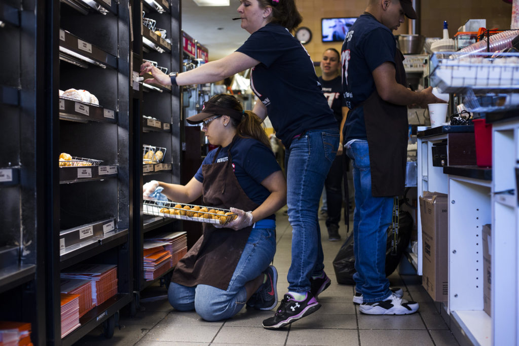Jennilease Gomez, 17, shifts trays of donuts at the Dunkin Donuts where she works on the weekends in South Hadley, Mass., on Saturday, September, 10, 2017. Gomez said she originally got the job in order to help support her brothers, 11 and 7, as her mother has a hearing disability which holds her back from working. This year she bought her siblings' school clothes. (Photo by Brittany Greeson)