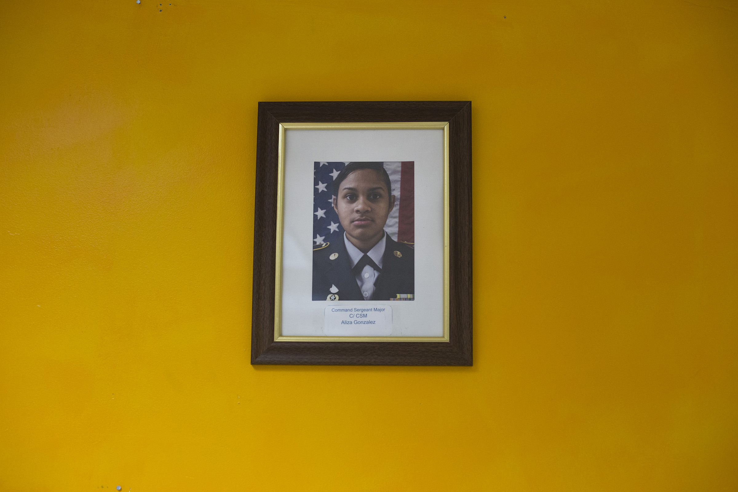 A single photograph featuring Command Sergeant Major Aliza Gonzalez, 17, hangs on the wall in a JROTC classroom in Springfield, Mass., on Monday, September, 11, 2017. (Photo by Brittany Greeson)