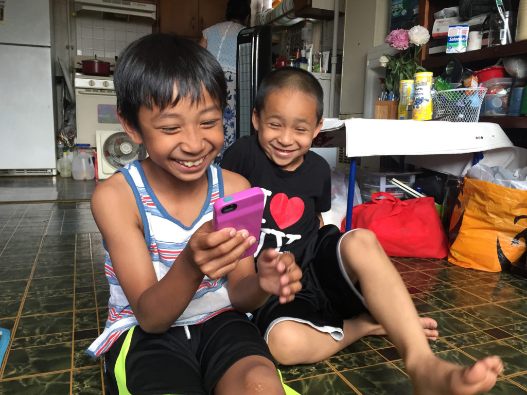 Nine-year old Maddox uses an app to help translate the words he doesn't know in Cambodian when he accompanies his grandmother to her doctor's visits, where she's treated for symptoms of PTSD. (Photo by Heidi Shin)