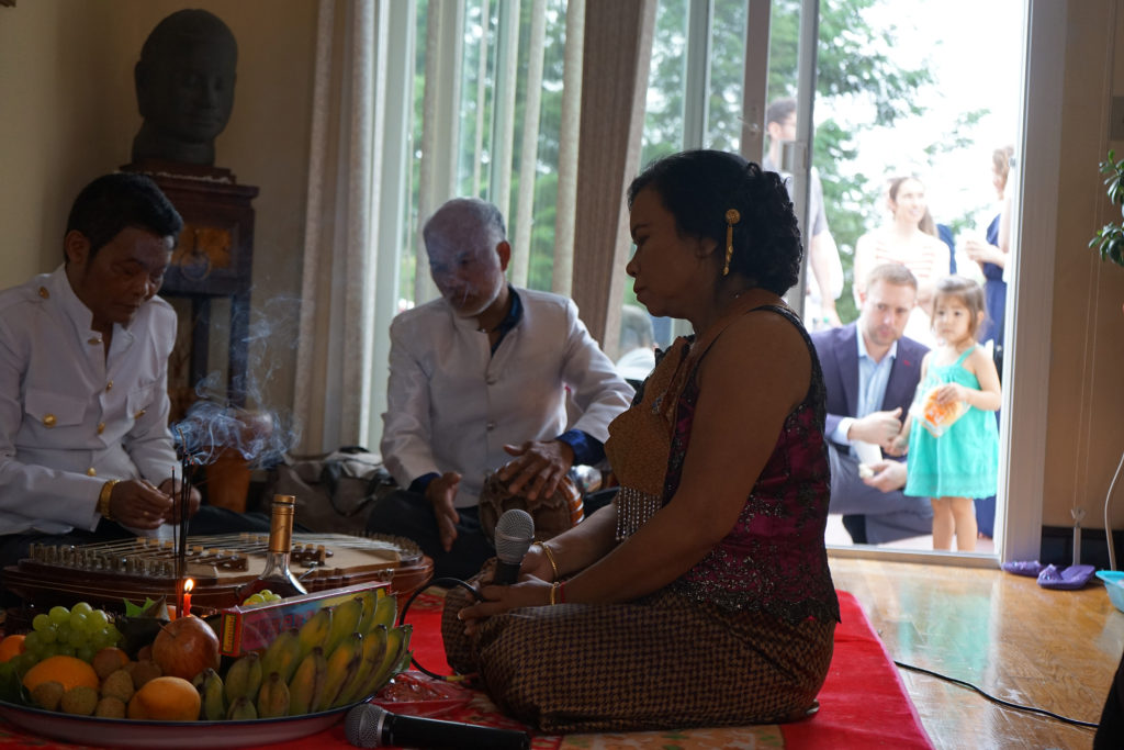 Sovann Khon and his band perform at a Cambodian American wedding in the suburbs of Boston. Curious guests listen from the back porch. (Photo by Heidi Shin)