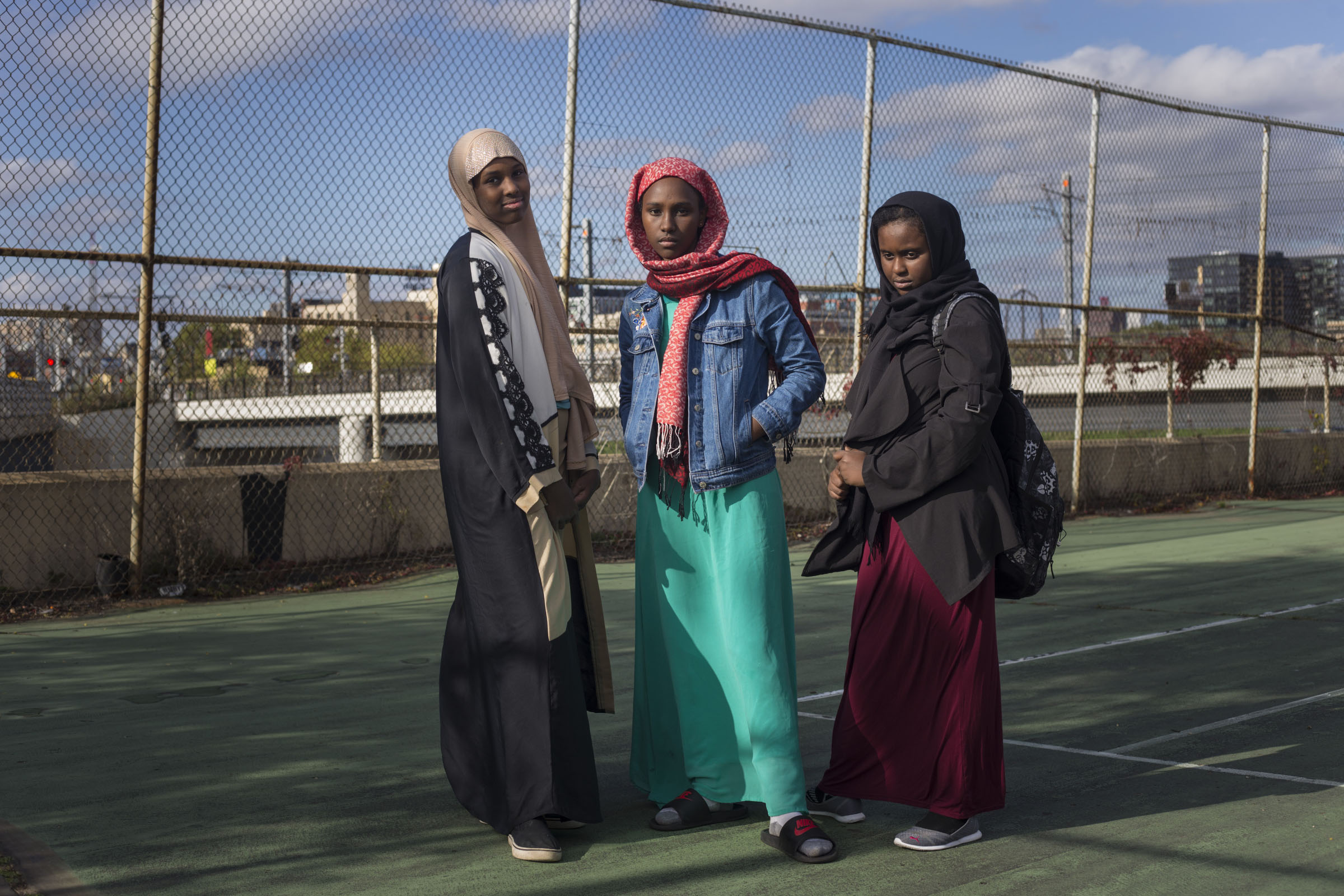 From left to right, Maryam Warsame, 13, Nada Tohu, 13, and Ikran Ibrahim, 12, outside of the Brian Coyle center in the Cedar-Riverside neighborhood of Minneapolis, Minn., on Thursday, October 12, 2017. (Photo by Brittany Greeson)