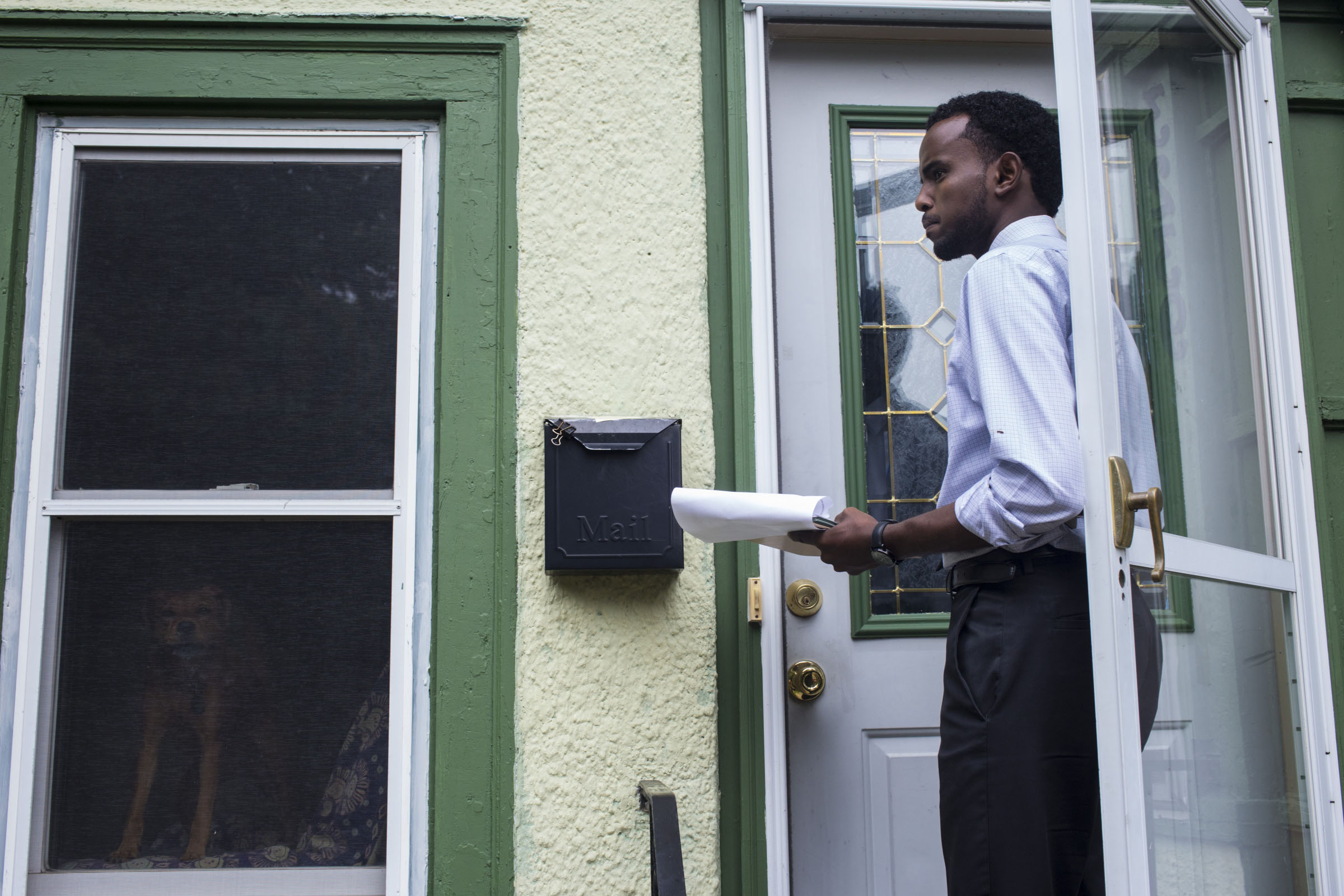 AK Hassan, 26, goes door to door while campaigning for Minneapolis Park Board in Longfellow, Minneapolis, Minn., on Saturday, October 7, 2017. If elected, Hassan said he would be the first Somali and youngest person to ever serve on the park board. (Photo by Brittany Greeson)