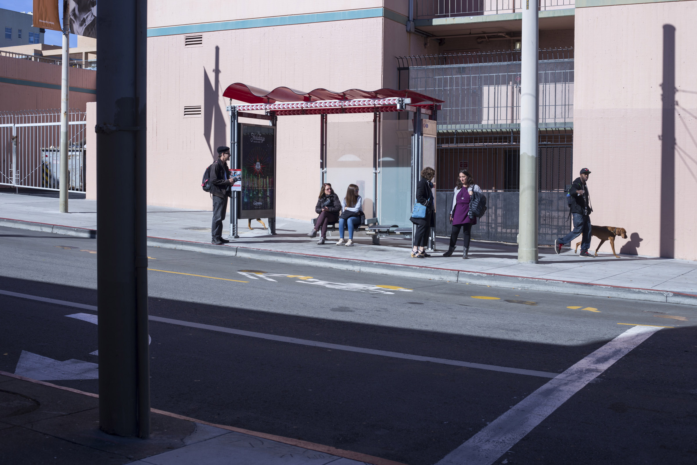 People wait for a bus in the Fillmore District of San Francisco, California, on Tuesday, November 7, 2017. (Photo by Brittany Greeson)
