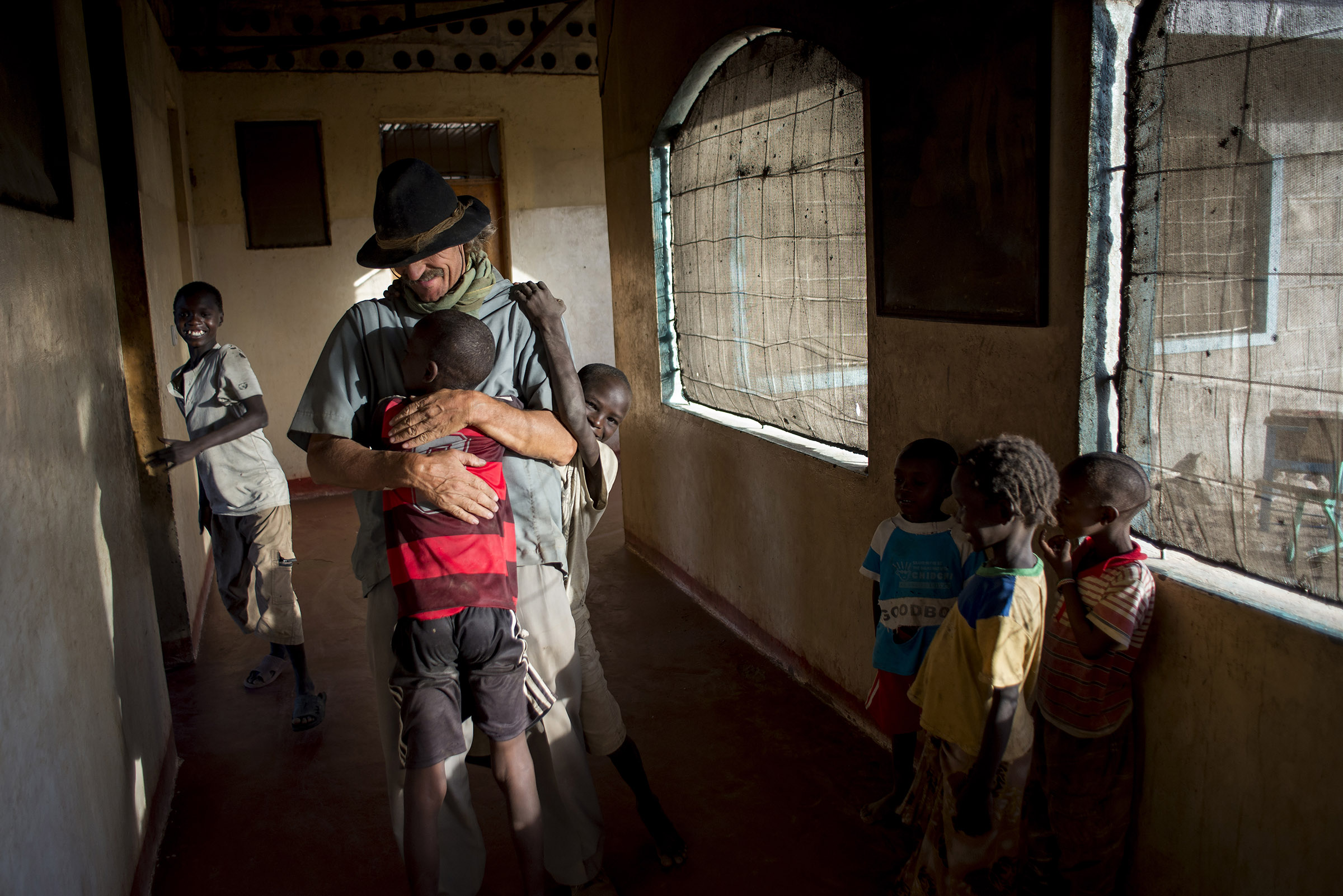 Father Florian is greeted by children after returning to Illeret, Kenya from a recent trip to Nairobi. The distance between the two cities is about 1000 km and takes almost three days to travel. (Christena Dowsett/The GroundTruth Project)