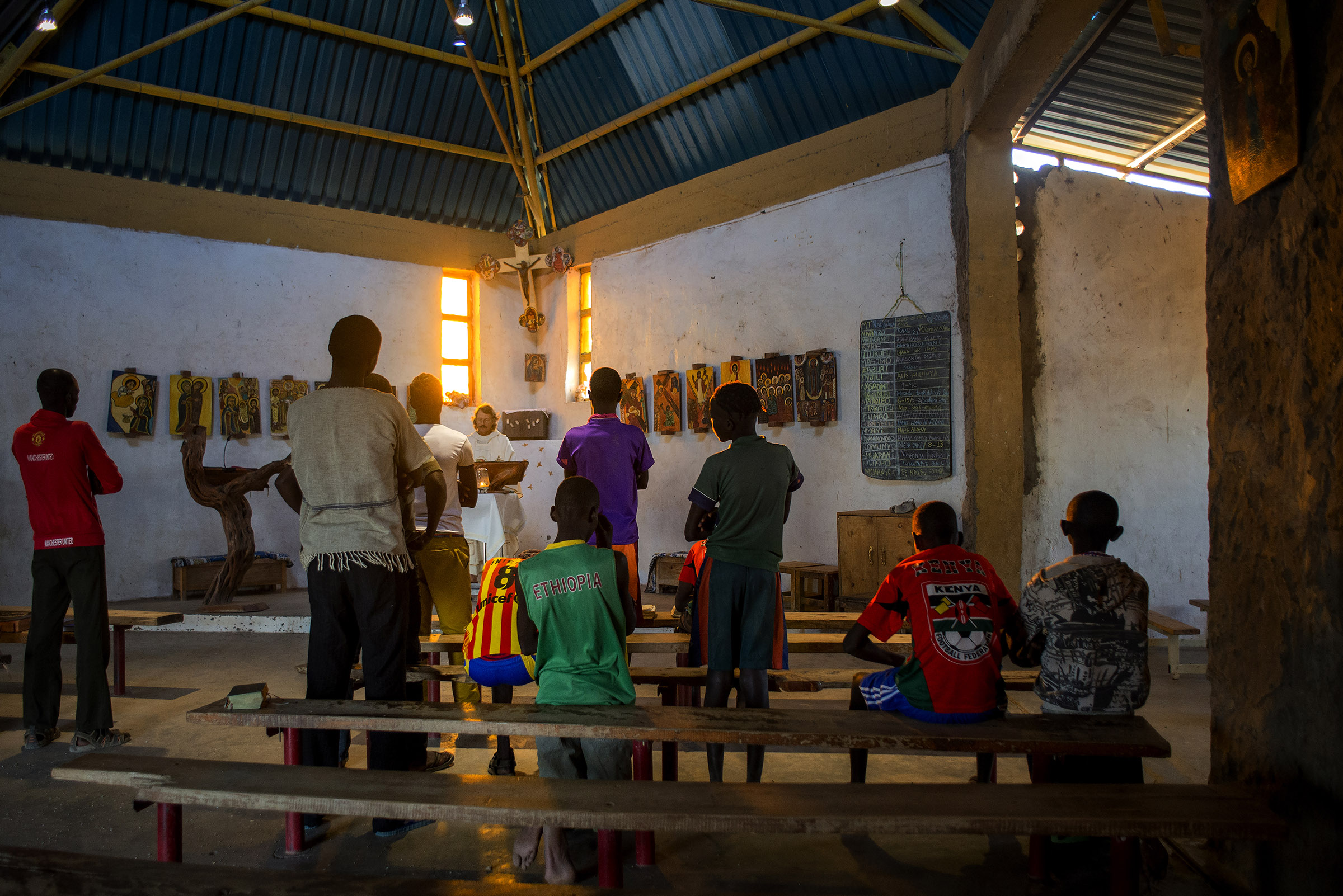 """Father Florian gives an afternoon service in Illeret, Kenya. He took his vows at St. Ottilien Archabbey, where he adopted the Benedictines' unofficial motto, """"Ora et Labora"""" — """"Pray and Work."""" This has become his mantra for his time with Kenya's ethnic Daasanach community, one of the smallest tribes in Kenya. (Christena Dowsett/The GroundTruth Project)"""