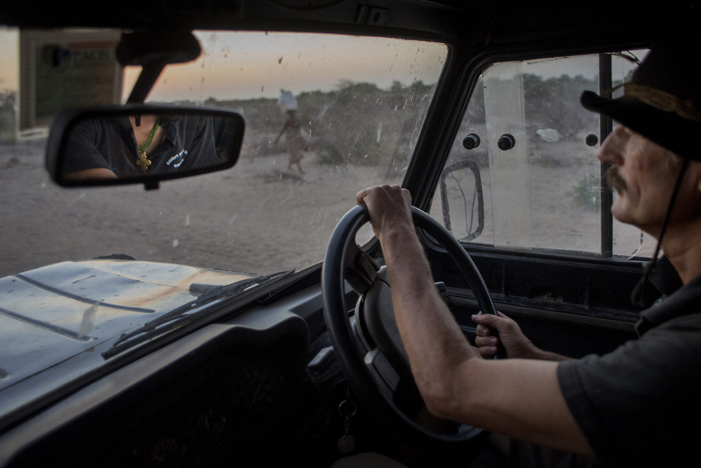 """Even in the ten years that Father Florian has lived with the community, he has seen serious changes in the environment. """"This is not a desert yet,"""" Florian says as he watches wind carry waves of sand across the horizon. """"But it will be soon."""" (Christena Dowsett/The GroundTruth Project)"""