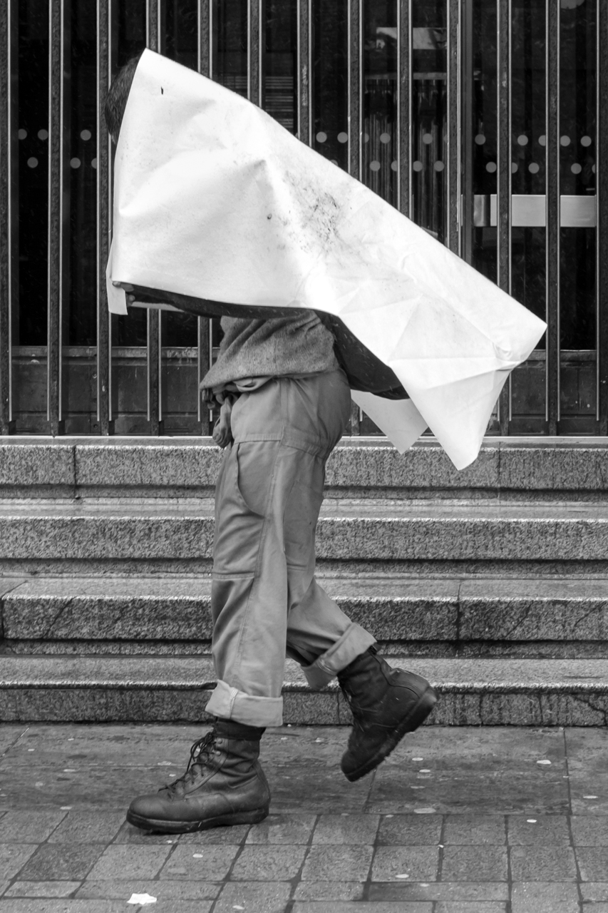 A man holds a tarp to shield himself from the sun. June 26, 2015. (Juan Cristóbal Cobo)