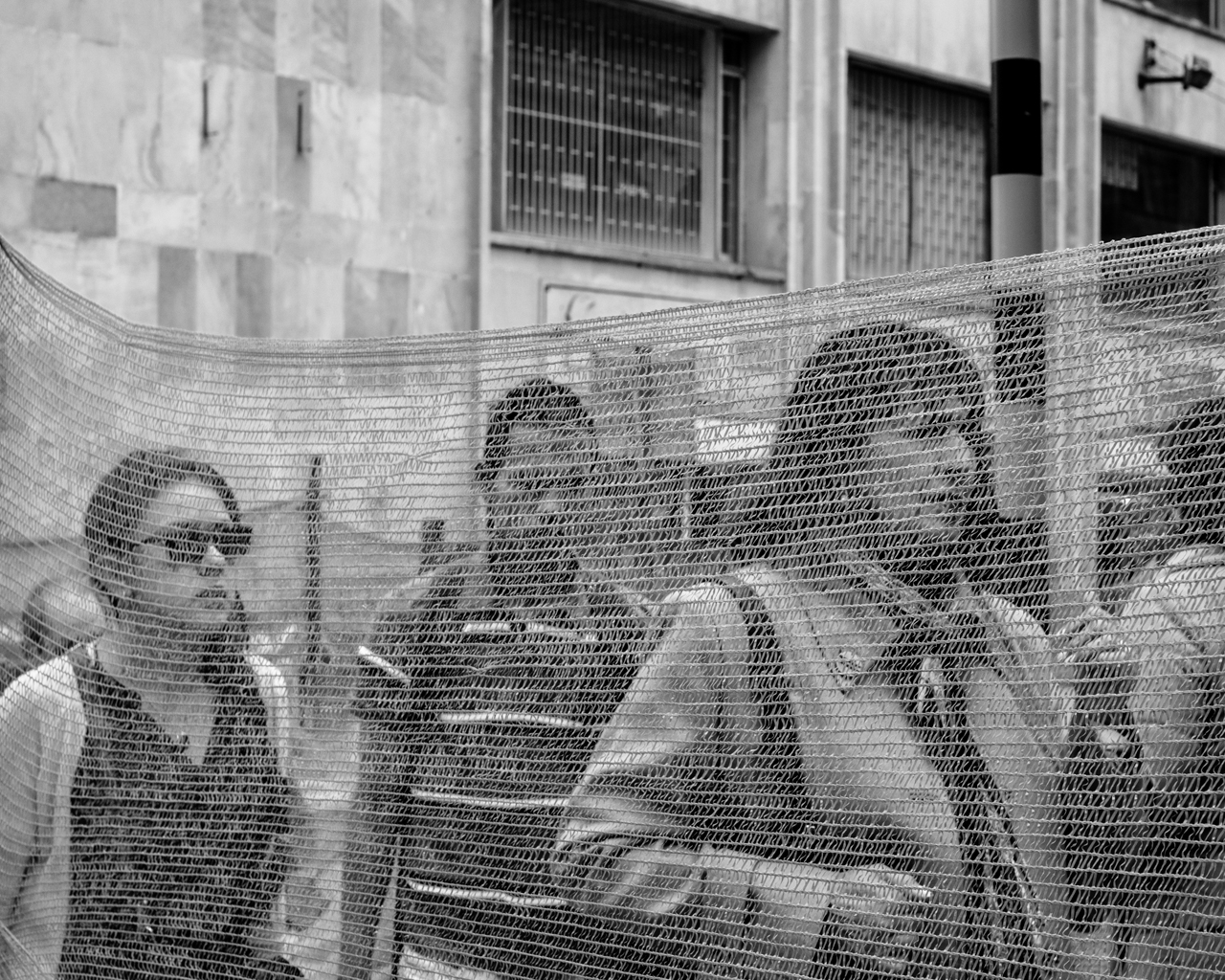 Passersby walk behind a net used to keep people away form ongoing construction on July 2, 2015. (Juan Cristóbal Cobo/The GroundTruth Project)