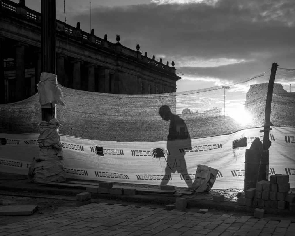 A man walks behind a construction barrier in the Plaza de Bolivar. In the background, the Colombian Congress Building. July 25, 2015. (Juan Cristóbal Cobo/The GroundTruth Project)