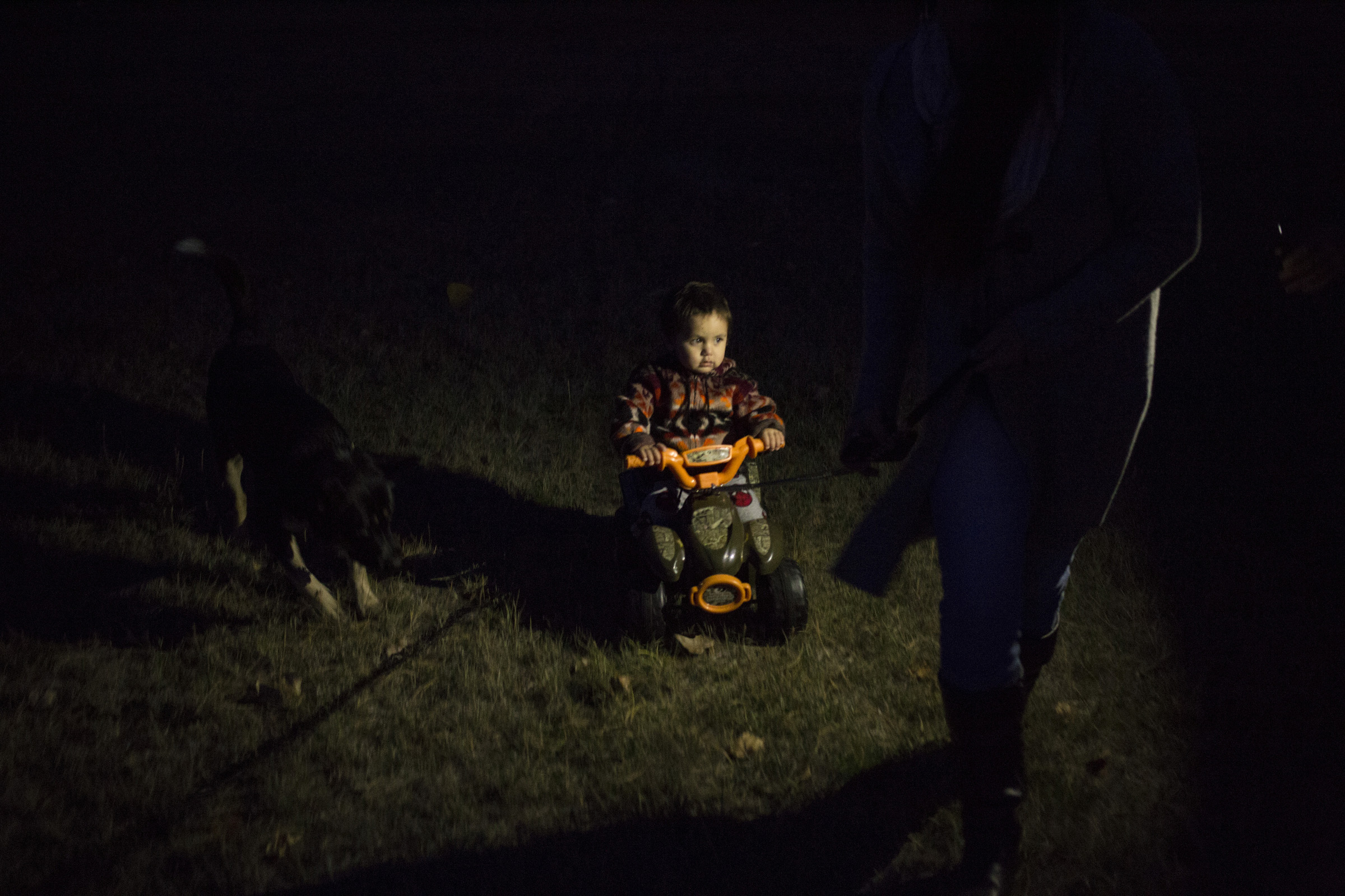 Niste Omeasoo, 2, is pulled across his yard on a tricycle by his grandmother, Susie Boushie, 37, in, Pablo, Montana, on Sunday, October 22, 2017. (Photo by Brittany Greeson)