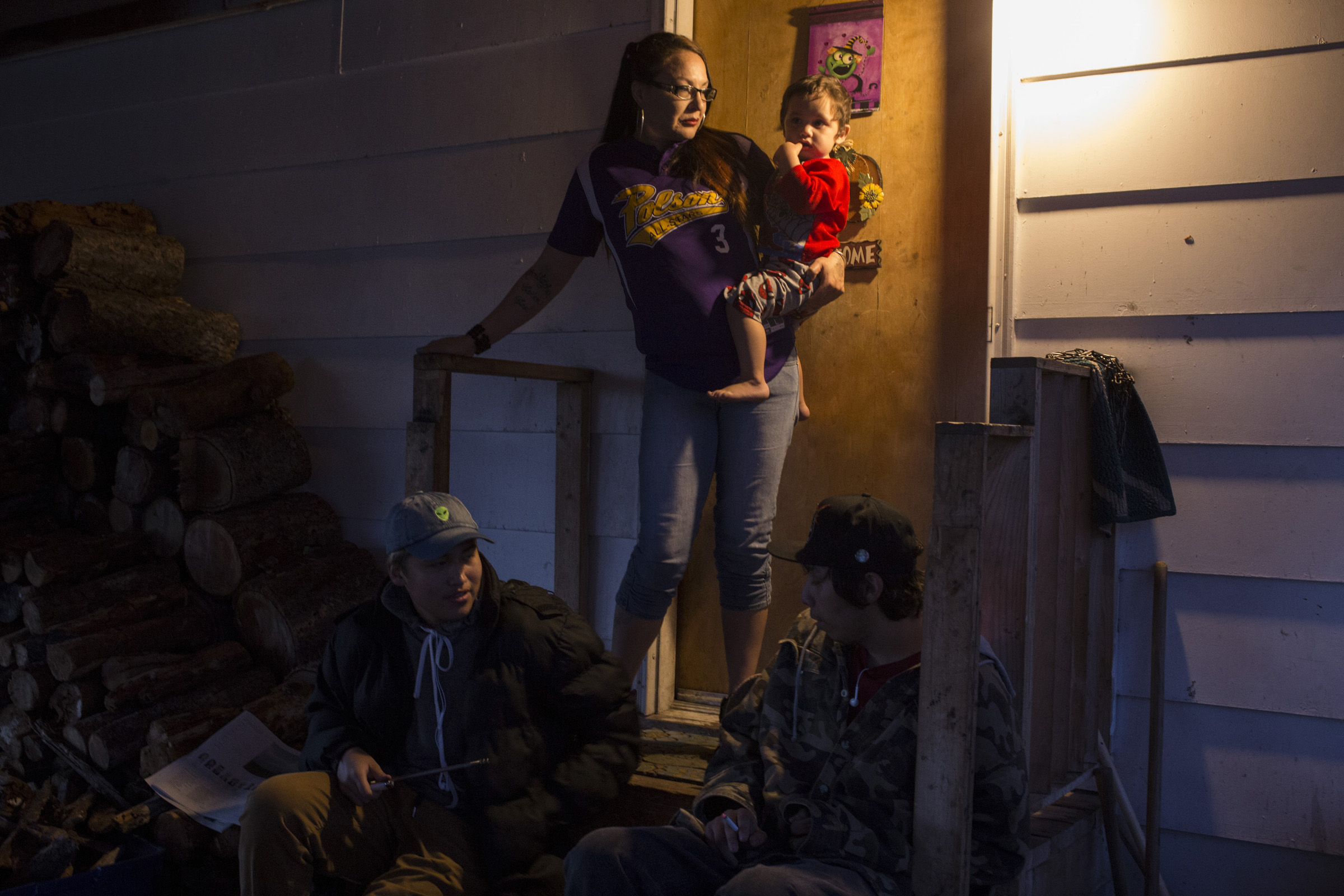 Susie Boushie, 37, looks out from her front porch while holding her grandson, Niste Omeasoo, 2, as two of her son's friends sit on their porch at their home in Pablo, Montana, on Sunday, October 22, 2017. (Photo by Brittany Greeson)