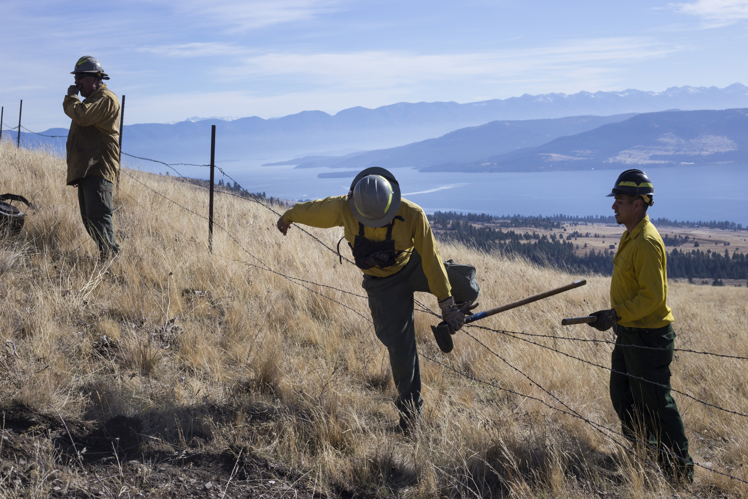 Members of the Confederated Salish and Kootenai Tribes Division of Fire cross over a barbed wire fence after preparing a barrier for a prescribed burn just along a ridge line outside of Elmo, Montana, on Tuesday, October 24, 2017. (Photo by Brittany Greeson)