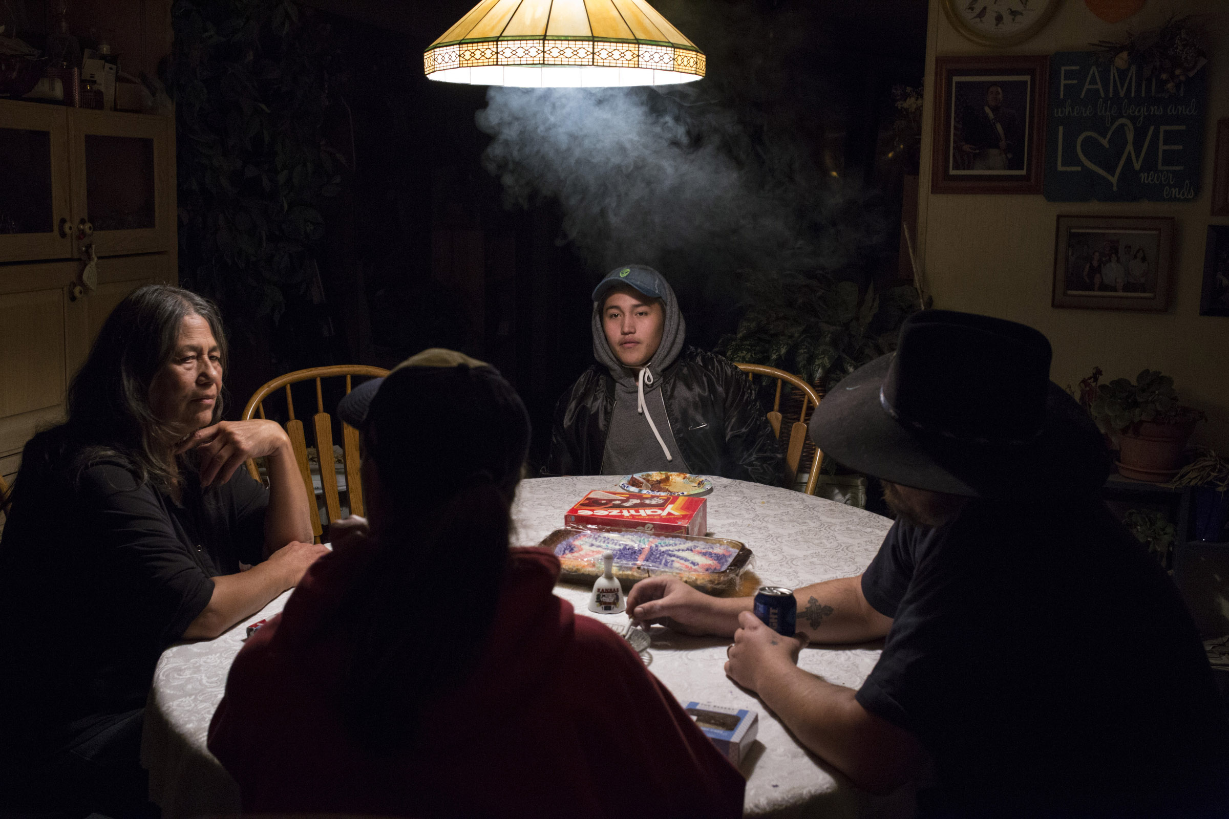 Xavier Smith, 17, sits at the kitchen table with his grandmother (left), mother (center), and his mother's boyfriend (right) at his grandmother's home in Pablo, Montana, on Saturday, October 21, 2017. (Photo by Brittany Greeson)
