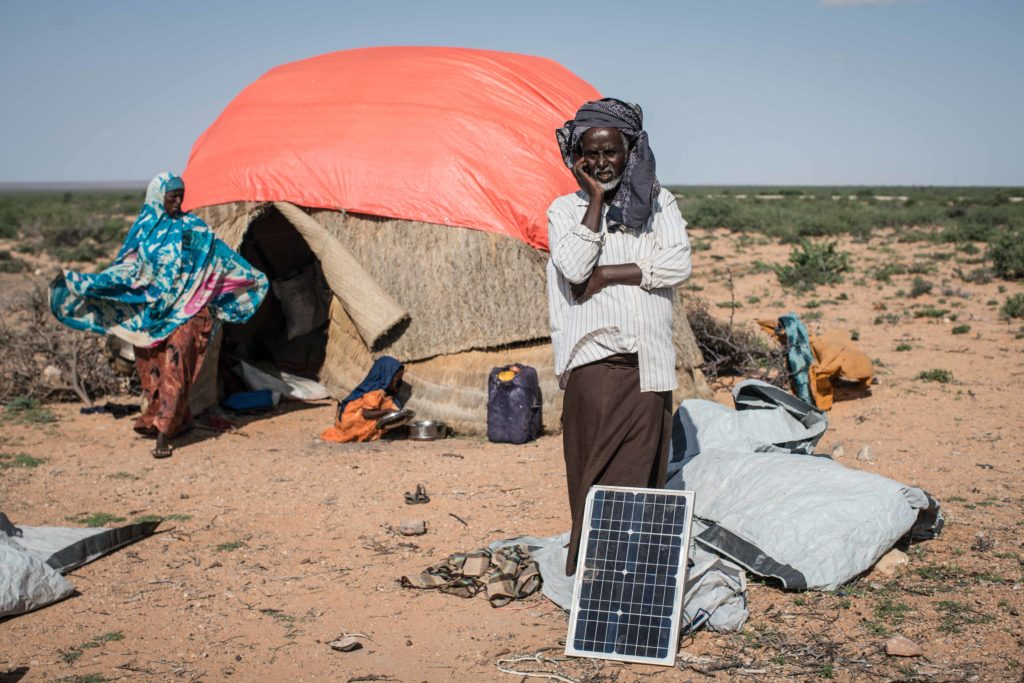 A man stands behind a solar panel in front of his home in Somalia as he talks on his cell phone. (Photo by Nichole Sobecki)