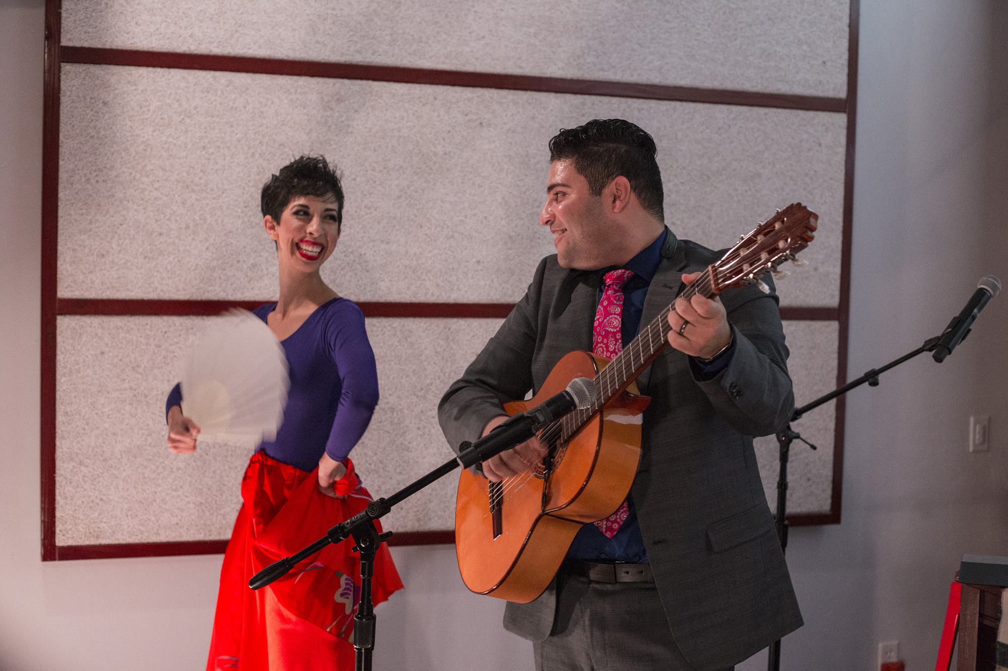 Omar locks eyes with his wife, Jasmín, on stage, as violinist Patrick Contreras makes his way offstage and into the crowd during the final number of their performance. (Brittany Greeson/The GroundTruth Project)