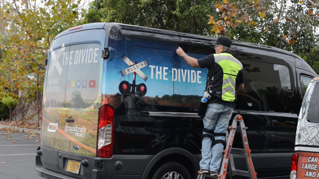 """JC strips the """"Crossing the Divide"""" wrap off the van. (Screenshot)"""