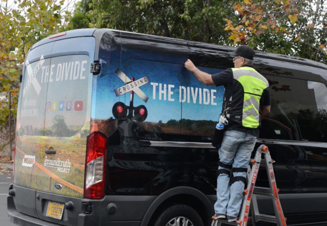 "JC strips the ""Crossing the Divide"" wrap off the van. (Screenshot)"