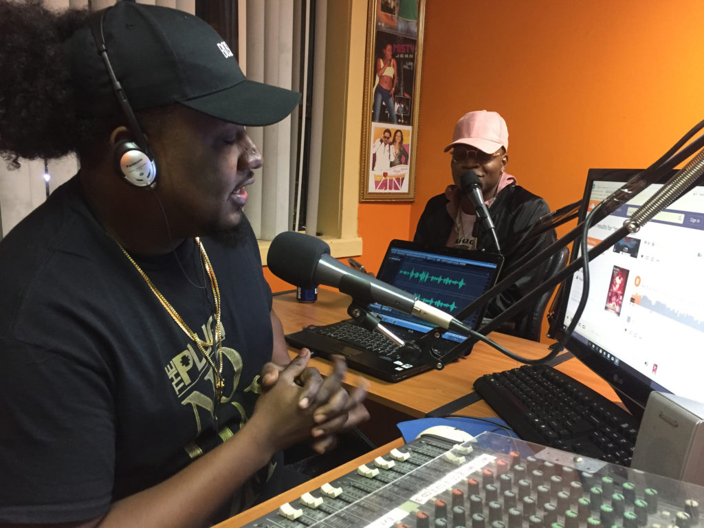 From left, radio host Sanders Nicolas and rapper Masterbrain talk live on air. (Photo by Ian Coss)