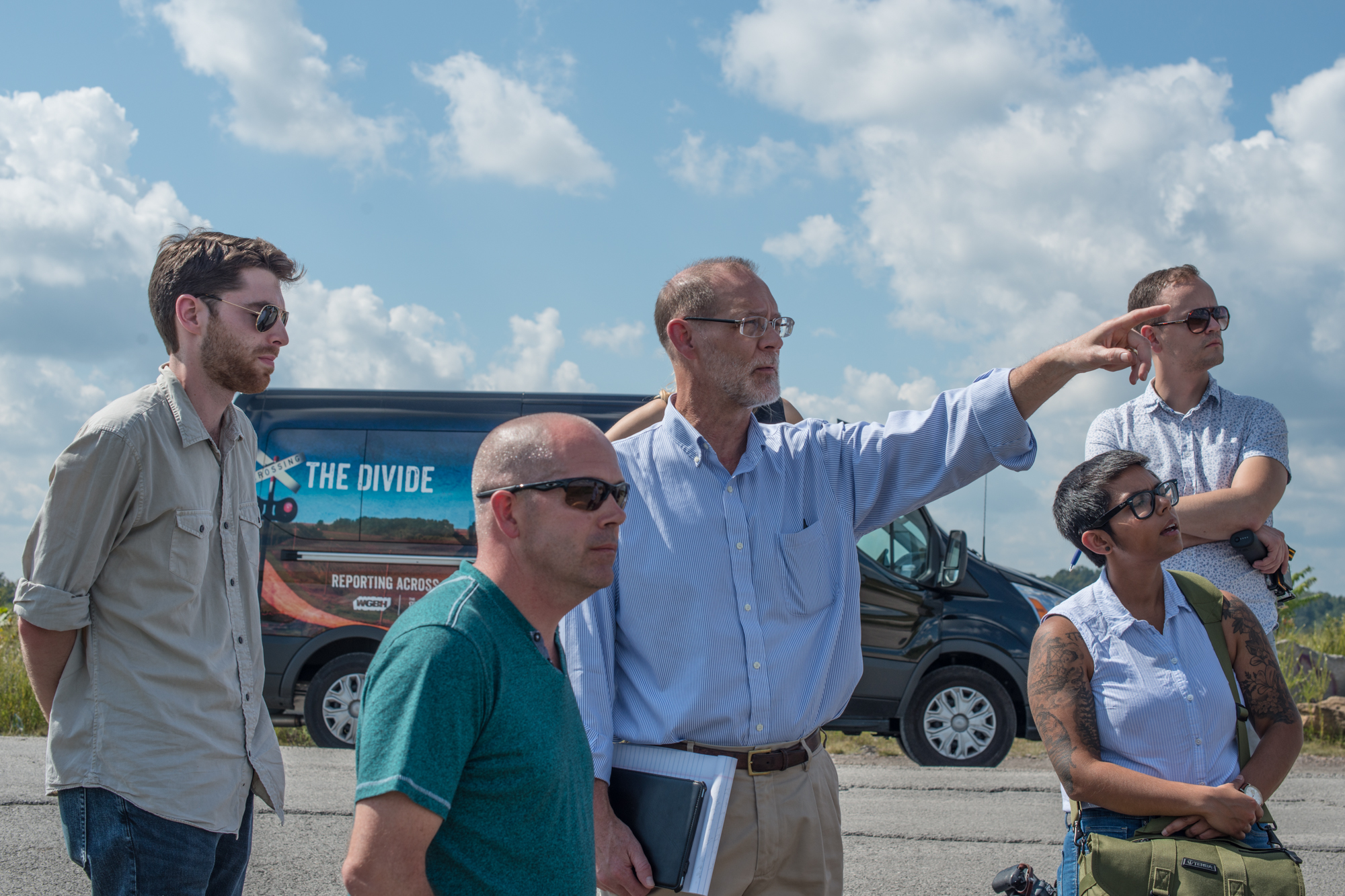 Bill Estep, (pointing, center) facilitated a visit to the site of a former strip mine. Also pictured, from left: Eric Bosco, former coal worker Kenny Stanley, Qainat Khan and Gabriel Sanchez. (Photo by Ben Brody/GroundTruth)