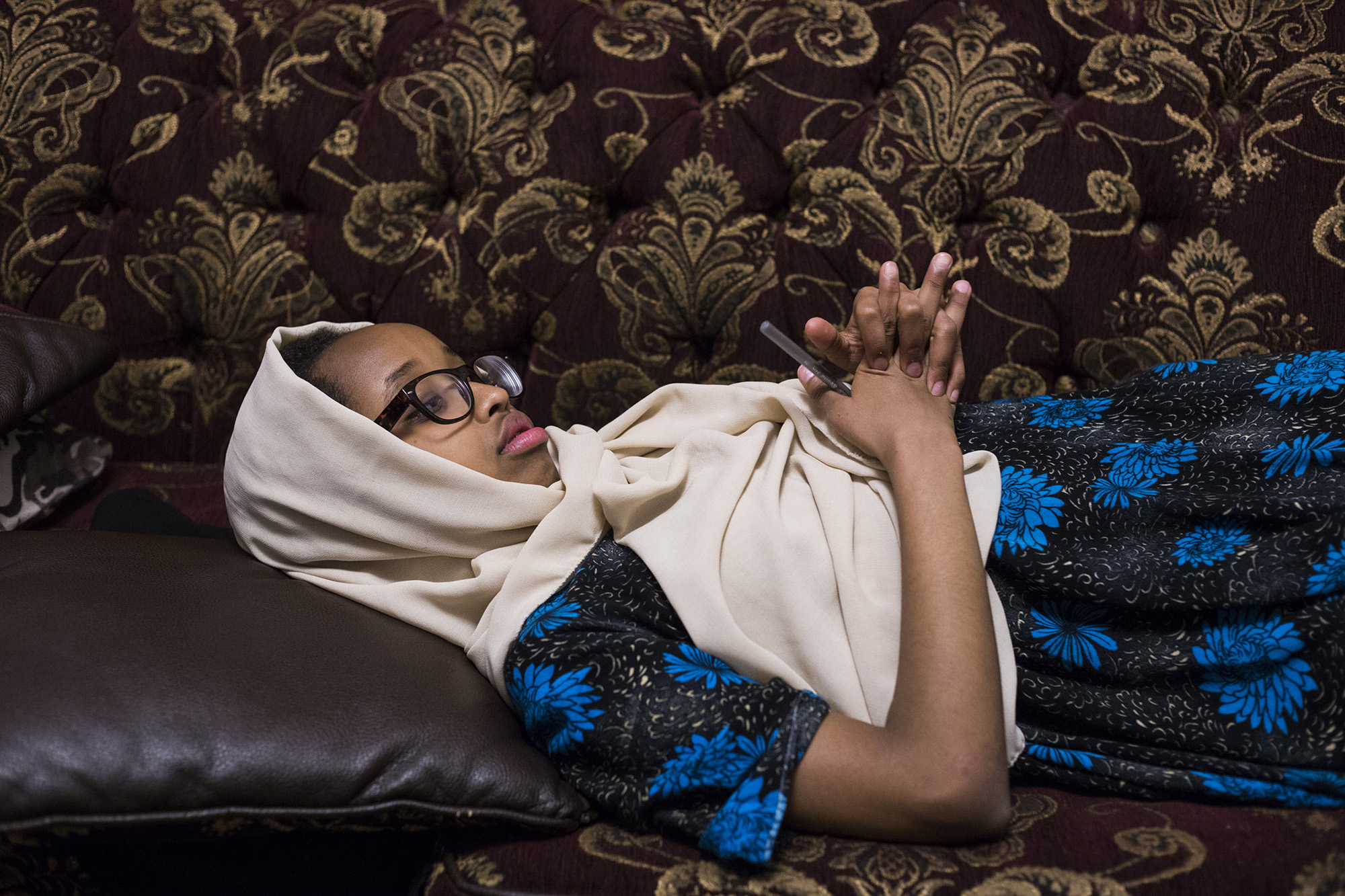 Aisha Mohamud, 13, lies on her couch as her mother, Waris Mohamud, helps her little brother, Abdullah, tell a classic Somali story at their home in Minneapolis, Minn., on Thursday, October 12, 2017. (Brittany Greeson/GroundTruth)