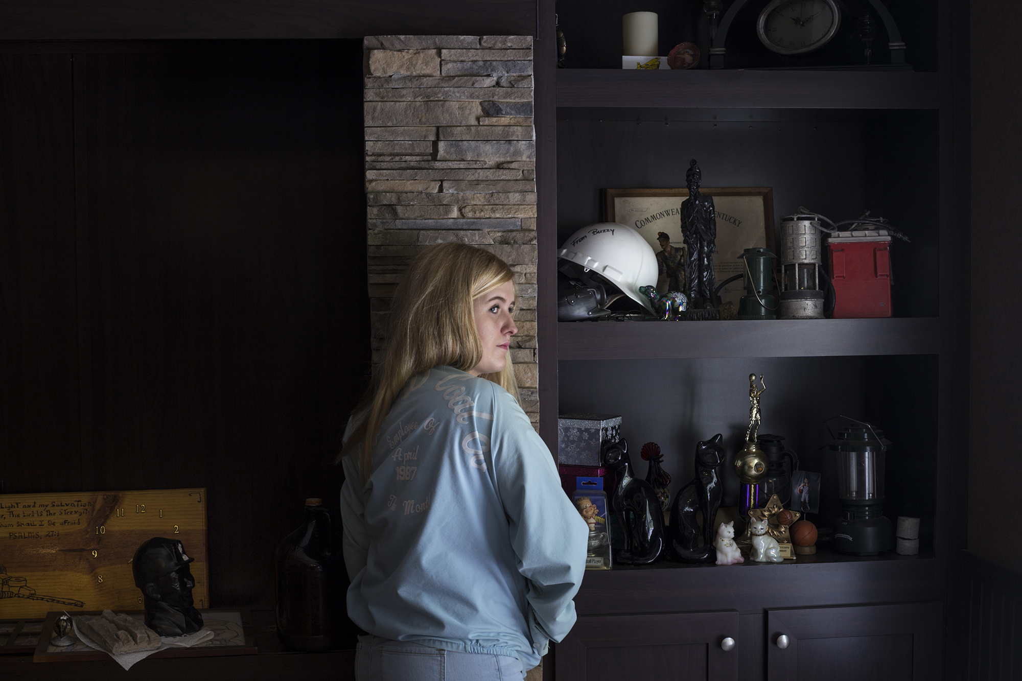 Lizzie Jones, 17, proudly wears her father's employee of the month jacket from his time working at the coal mines. She stands next to a shelf of her family's relics from the coal industry at her home in eastern Kentucky, on Sunday, September 24, 2017. Jones' father passed away from black lung disease in 2014. In January 2017, her mother, who also worked in the coal mining industry, passed away. Jones has developed a complex relationship with the coal industry that both built her community and stole her parent's life. (Brittany Greeson/GroundTruth)
