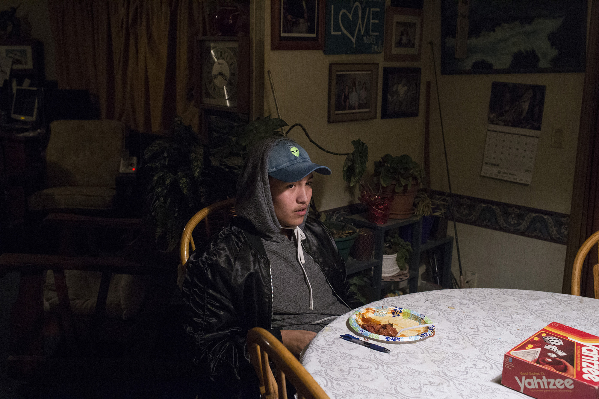 Xavier Smith, 17, who is Navajo and Filipino, sits at the kitchen table in his grandmothers home as his grandmother, mother, his mother's boyfriend enjoy a card game, in Pablo, Mont., on the Flathead Reservation on Saturday, October 21, 2017. (Brittany Greeson/GroundTruth)