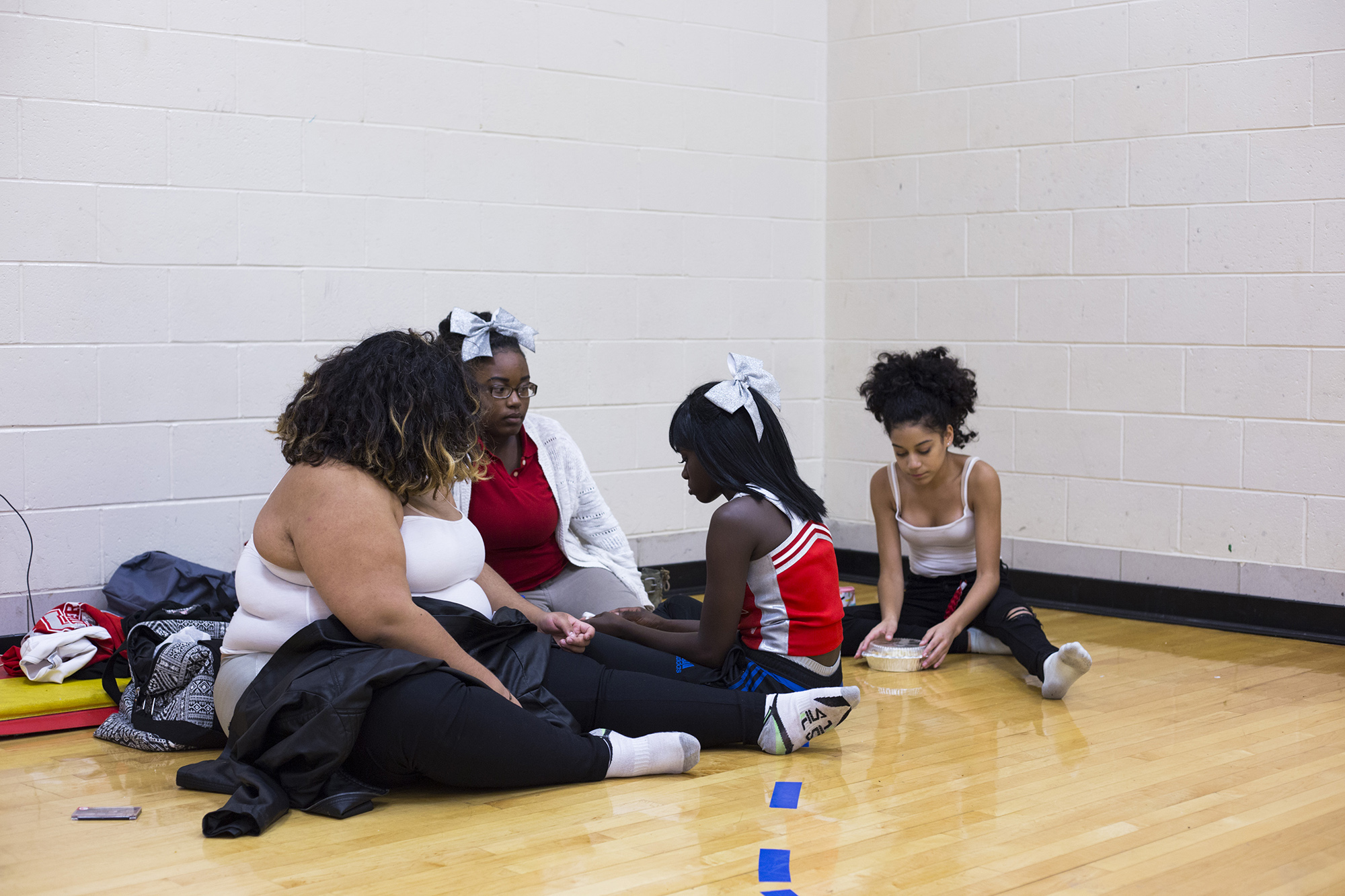 London Gladden, 17, (second from right) is consoled by her friends and teammates after a boy made a remark that made her cry before cheerleading practice at the High School of Commerce in Springfield, Mass., on Friday, September, 8, 2017. (Brittany Greeson/GroundTruth)