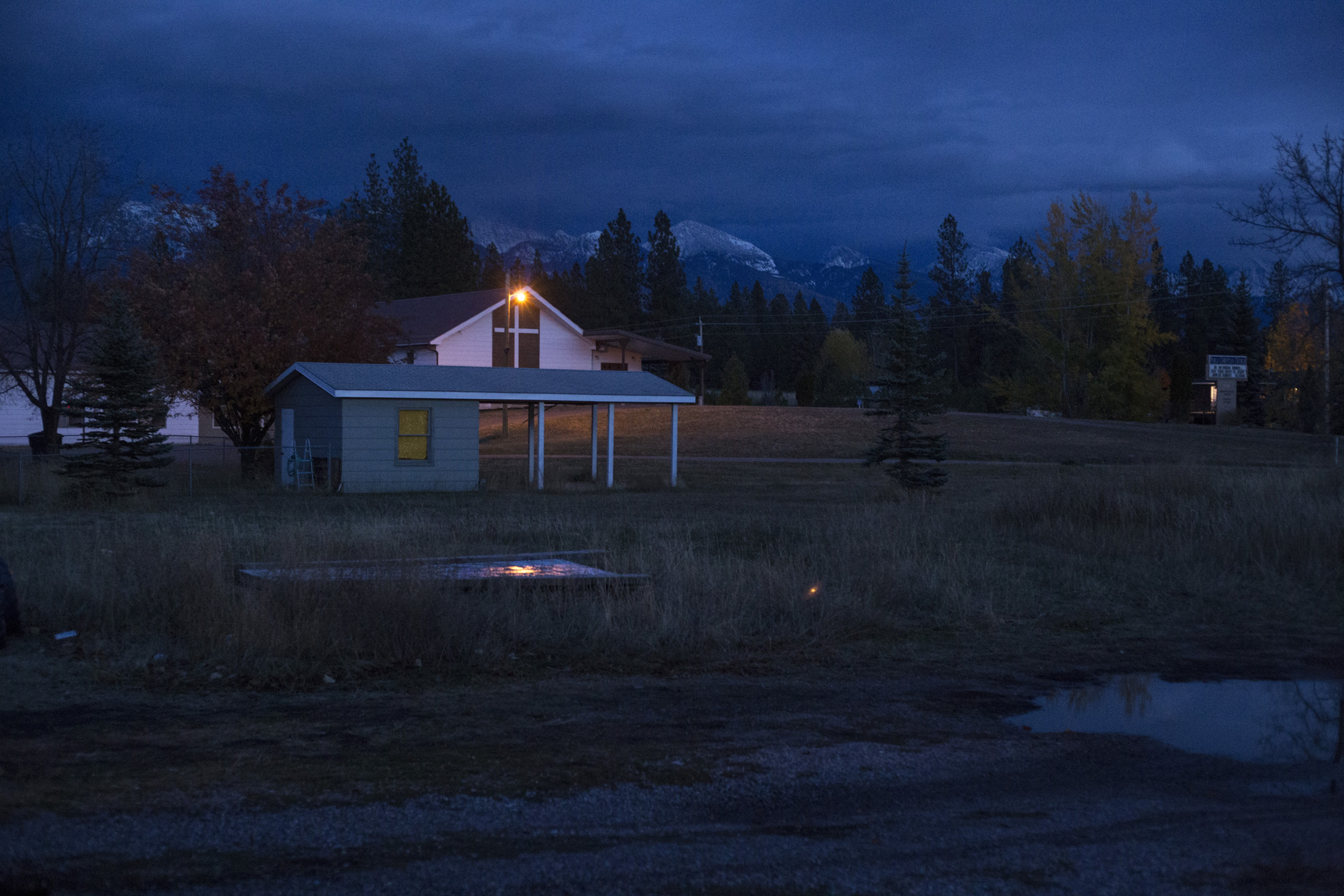A church light remains on as the sun falls behind the mountains at the edge of the Flathead Reservation in Pablo, Mont., on Sunday, October 22, 2017. (Brittany Greeson/GroundTruth)