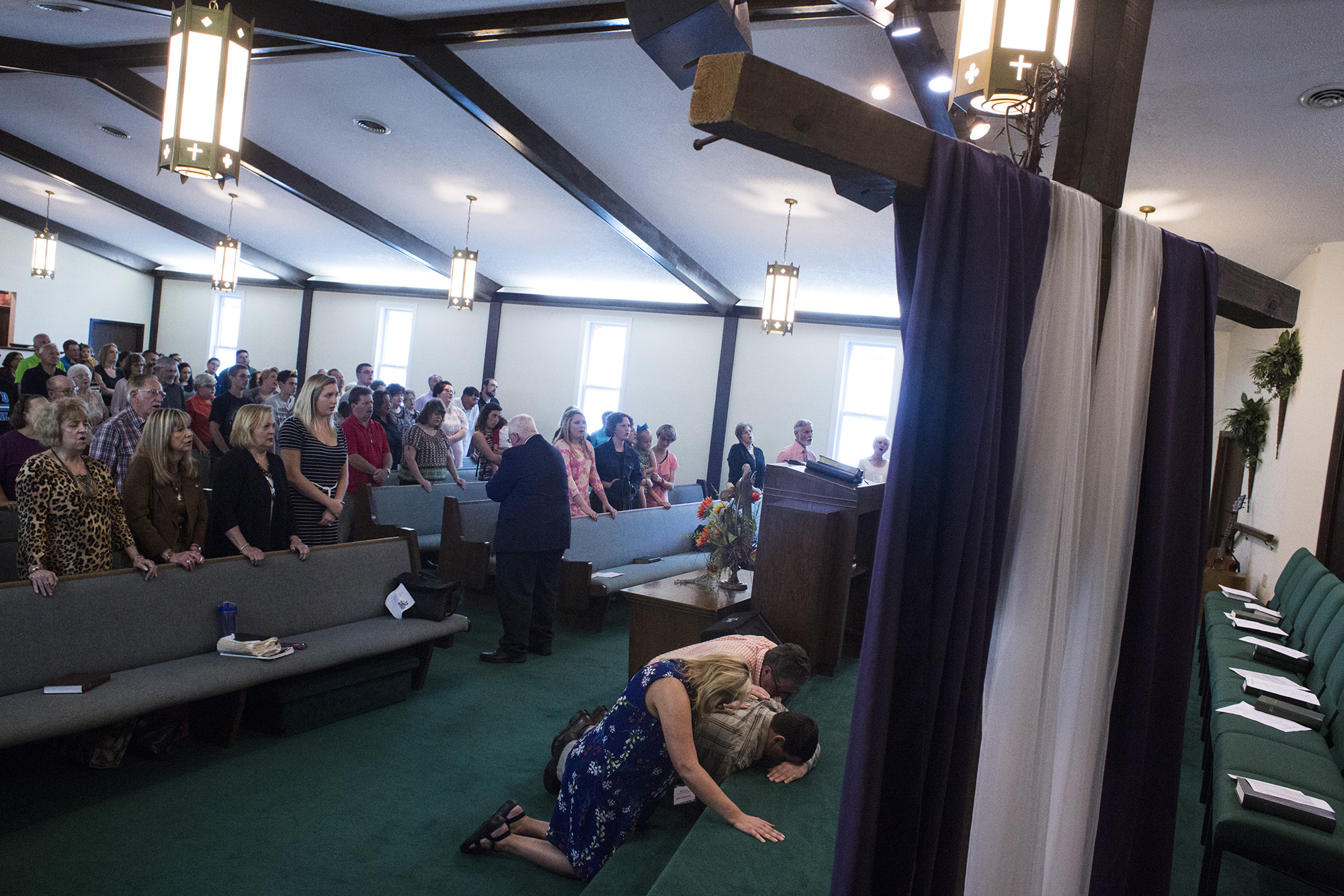 Mary Sloane, an English teacher at Floyd Central High School, prays for a member of her congregation at First Baptist Church in McDowell, Ky., on Sunday, September 24, 2017. (Brittany Greeson/GroundTruth)