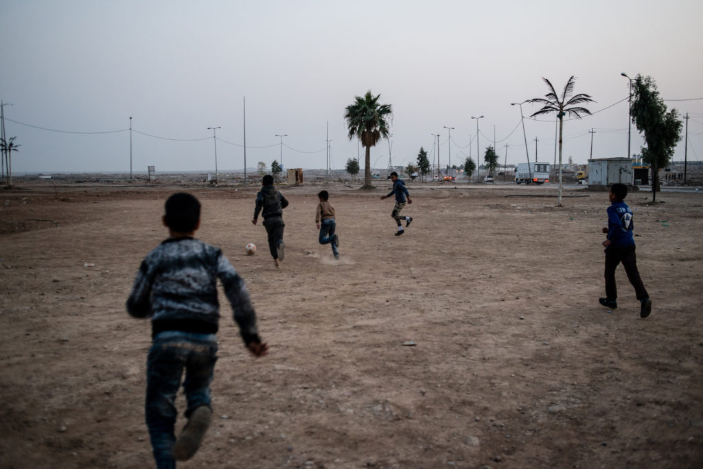 Iraqi children play football at Baghdad Circle, the entrance to West Mosul, on January 14, 2018. (Alex Potter/GroundTruth)