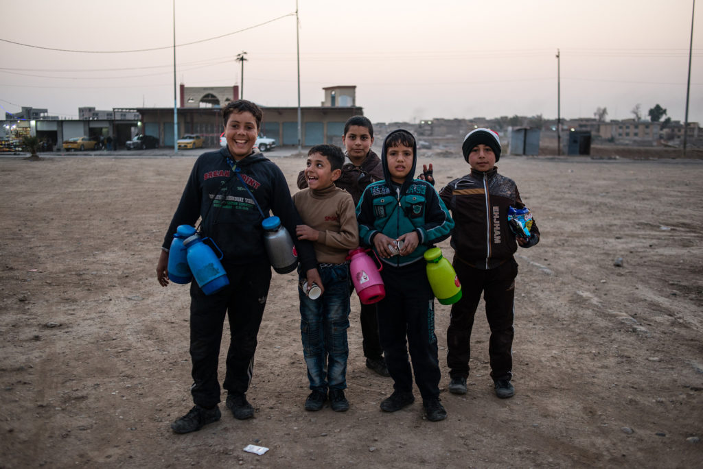Iraqi children sell tea and biscuits at a traffic intersection at the entrance to West Mosul on January 14, 2018. Though it was a school day, most of the children replied that they had to work to help support their families. (Alex Potter/GroundTruth)