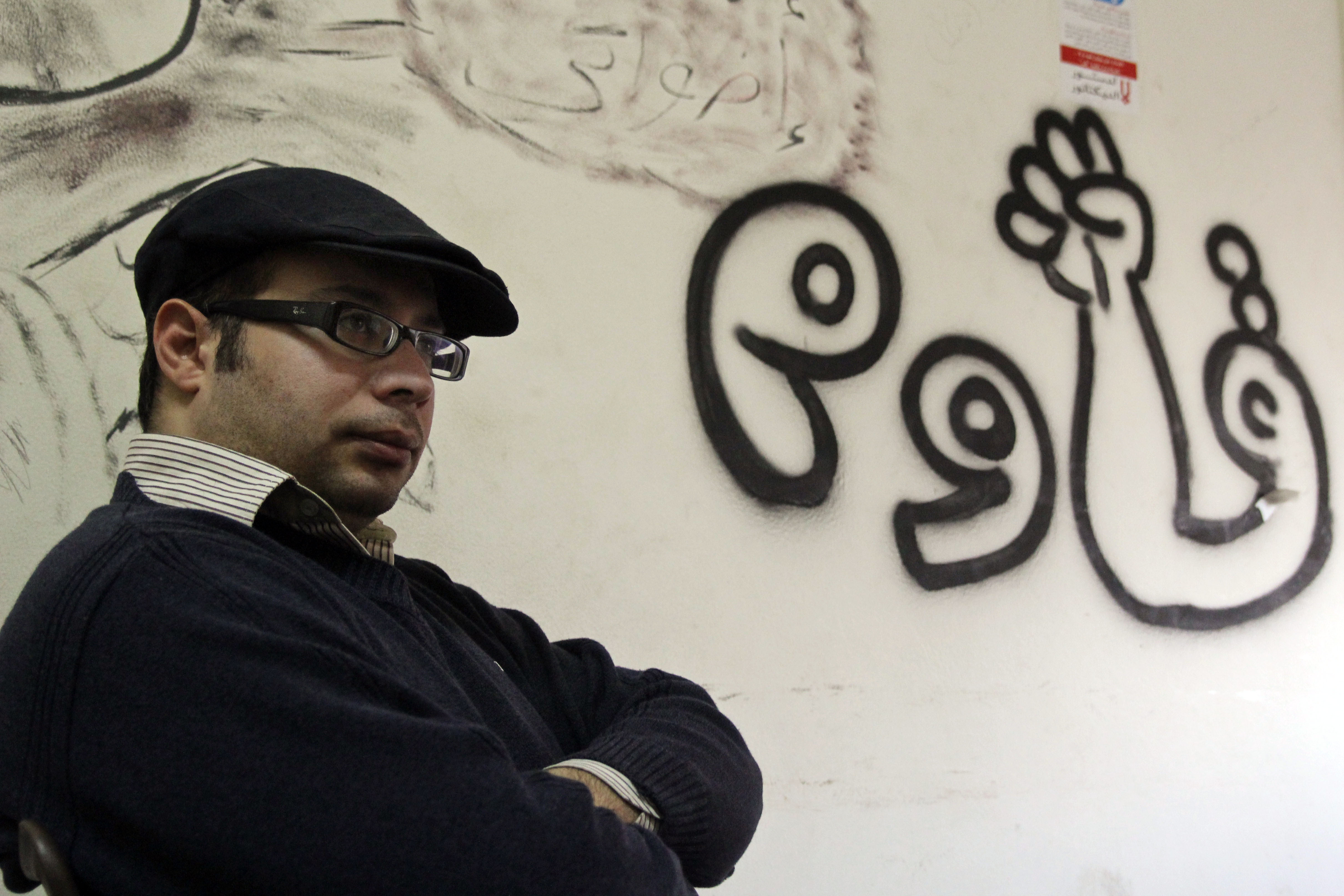 "Ahmed Maher photographed in January 2013, in the headquarters of the April 6 Movement. The writing on the wall reads ""resist."" (Roger Anis/GroundTruth)"