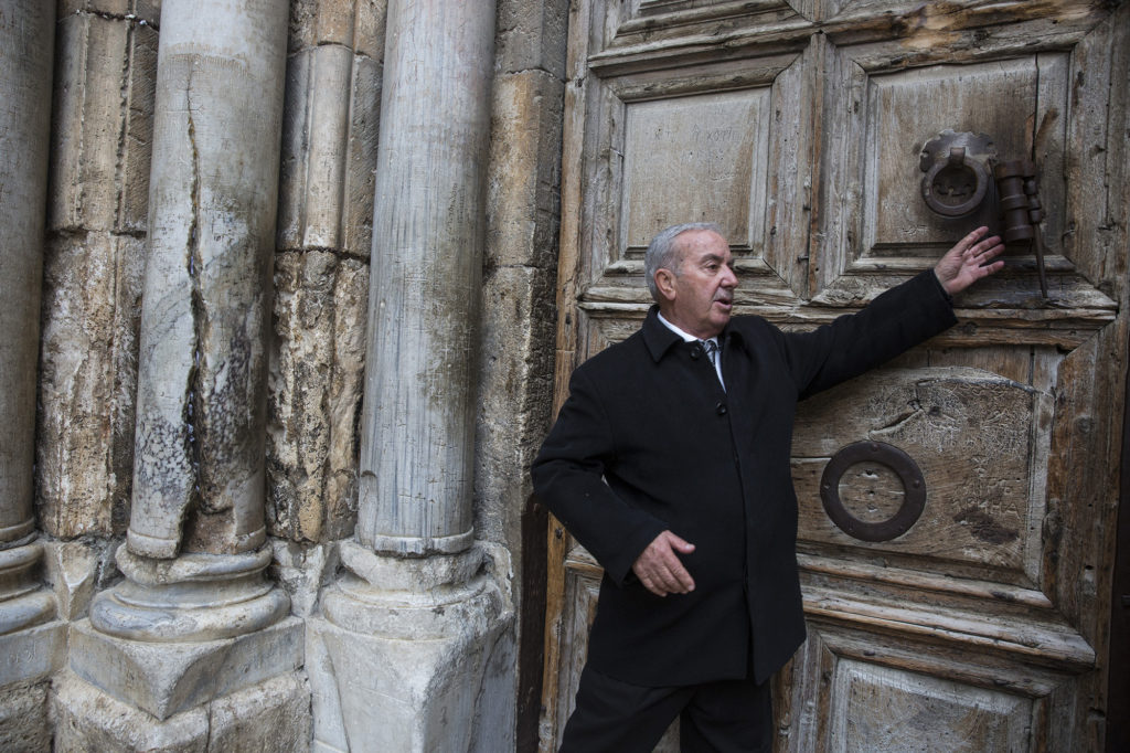 Mr. Wajeeh Nuseibeh outside one of the giant wooden doors of the Church of the Holy Sepulchre on Good Friday, March 30, 2018. The Nuseibeh family, a Muslim family, has been Door Keeper for generations. (Heidi Levine/The GroundTruth Project)