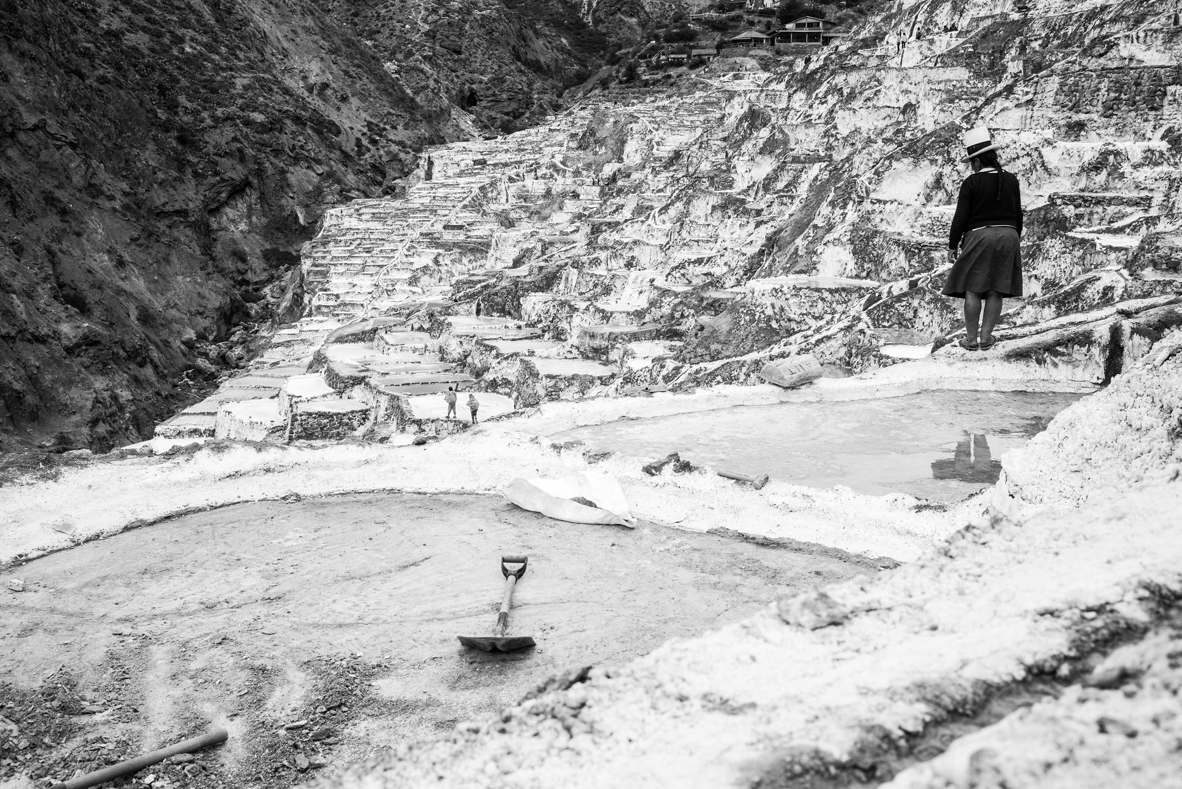 A woman works at Maras salt pans. For thousands of years, indigenous Peruvians have been gathering salt from these terraced hillsides. (Alessandro Cinque/GroundTruth)