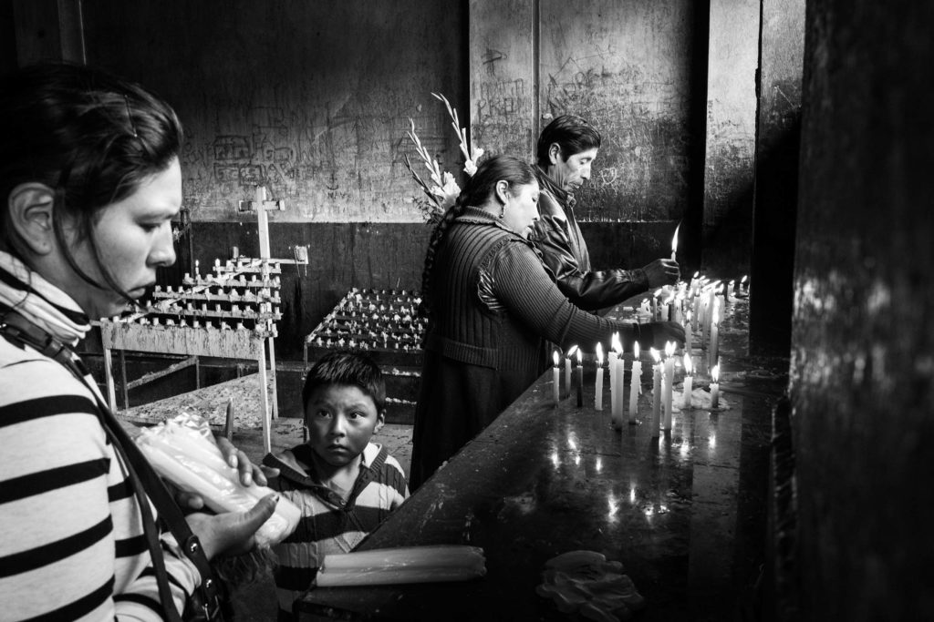 A family lights candles in a church after Mass on Sunday. The Catholic Church still has a strong presence, though most of the people are Quechua. (Alessandro Cinque/GroundTruth)