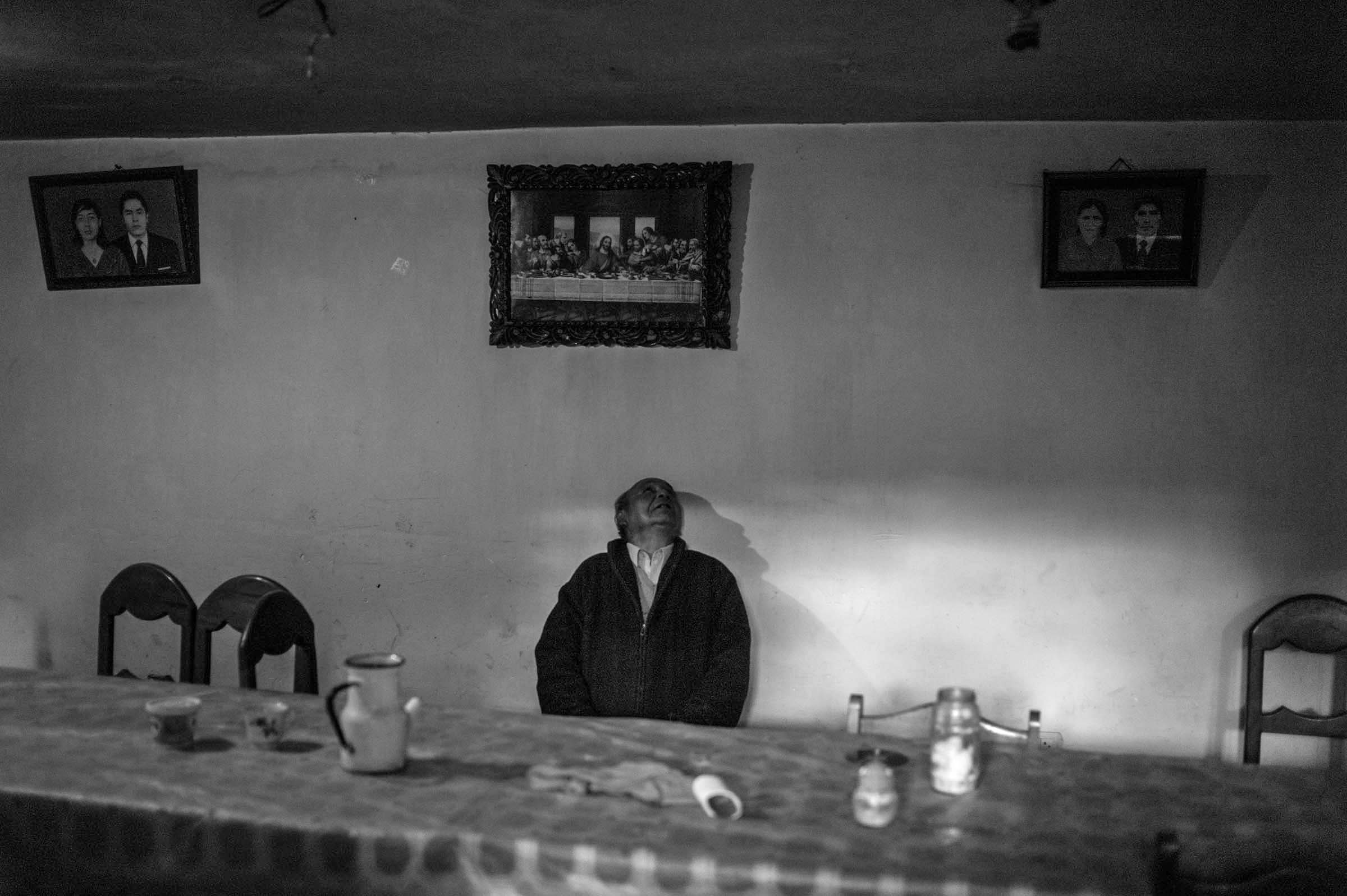 A man looks up at the image of the Last Super after a family meal in the Sacred Valley. (Alessandro Cinque/GroundTruth)