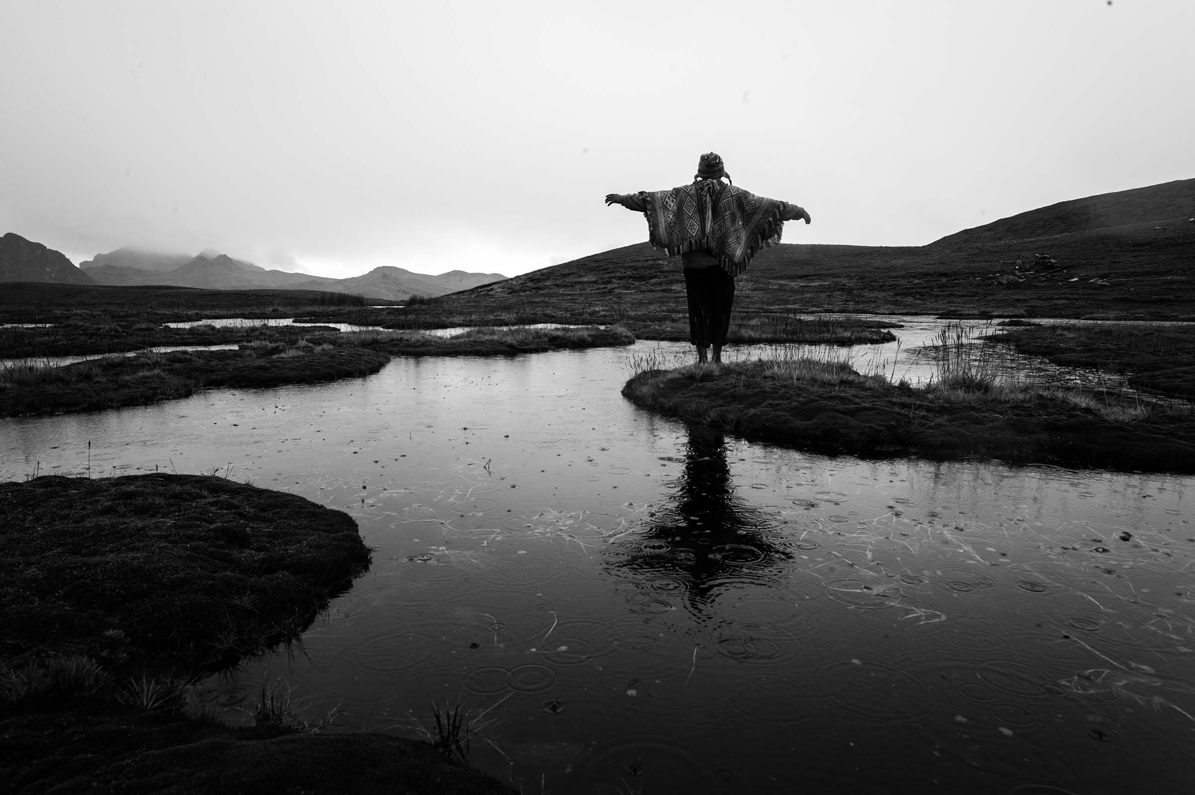 A man raises his arms towards the horizon in the Huarocondo District of Peru. (Alessandro Cinque/GroundTruth)