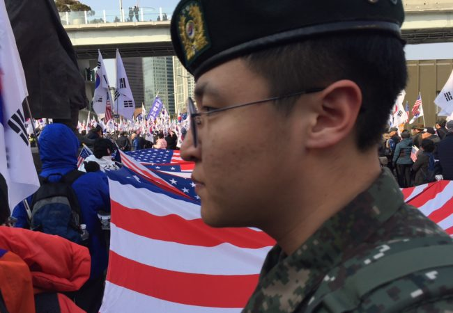A South Korean soldier walks through a political march near Seoul Station featuring thousands of Korean and American flags on Saturday, March 10, 2018. (Kevin Grant/GroundTruth)