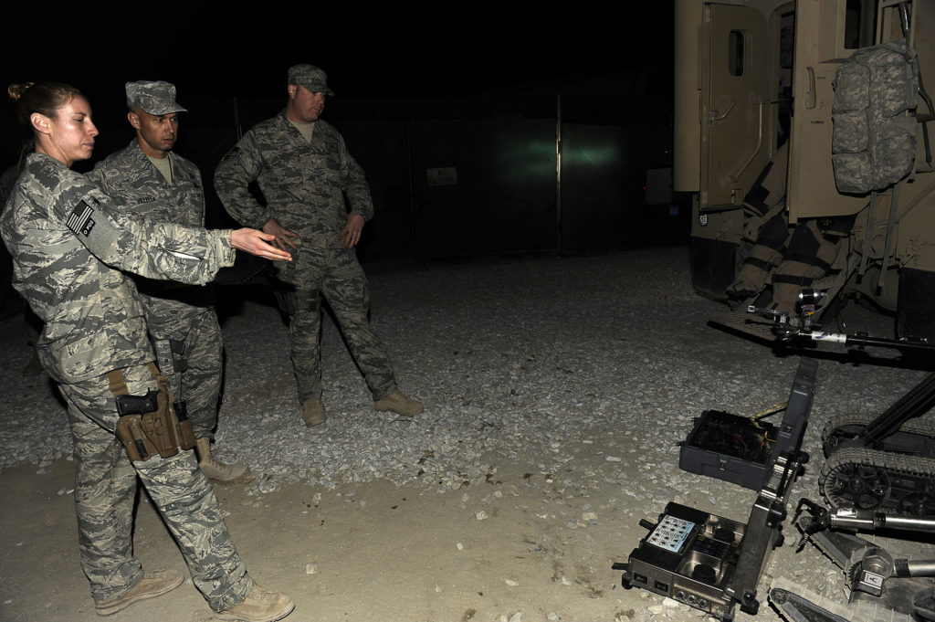U.S. Air Force Staff Sgt. Elizabeth Butler was one of the few women bomb techs on the Explosive Ordnance Division of the Air Force. She demonstrates a Packbot, a robot that helped her and her team disable IEDs, at Bagram Airfield in Afghanistan on Dec. 29, 2009. (Photo courtesy of Elizabeth Butler)