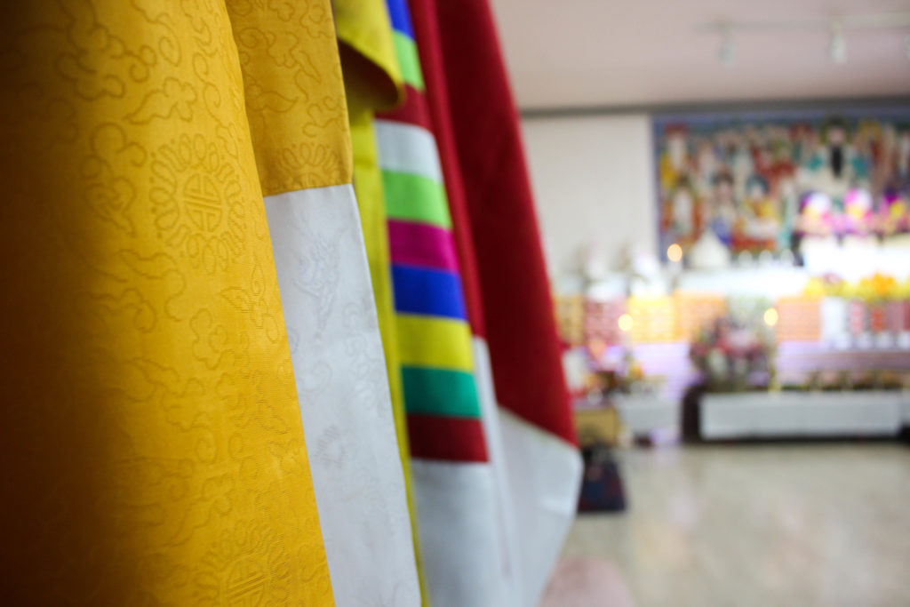 A collection of silk robes lines one of the walls. The five-hour ceremony is divided in shorter segments of about 30 minutes each. During each segment, the four shamans are believed to incarnate one of the many gods in Korean shamanism. Every time they did so, they changed the color of their robe. (Miranda Mazariegos/GroundTruth)