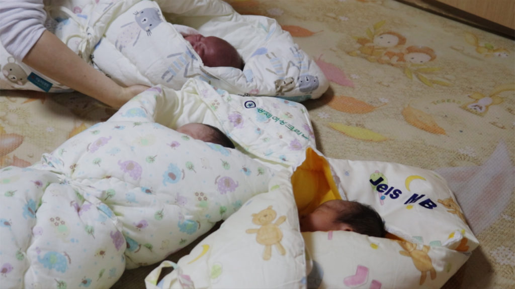 Three infants from the baby box are swaddled and ready to be transported to the public children's hospital. (Paulina Cachero/GroundTruth)