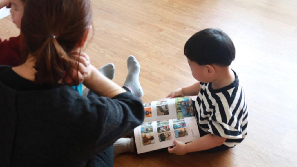A volunteer reads with an orphan at ShinMang Won Orphanage. (Paulina Cachero/GroundTruth)