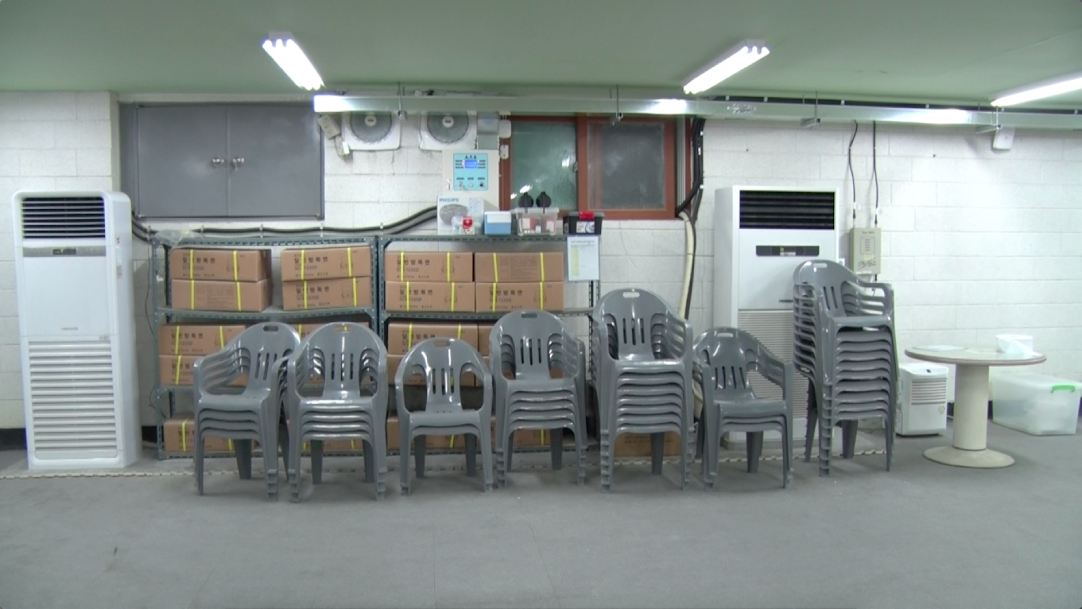 Plastic chairs, gas masks, and a Phillips CD player are stored for emergencies at an underground shelter near Tongil Chon's city hall. (Aziza Kasumov/GroundTruth)