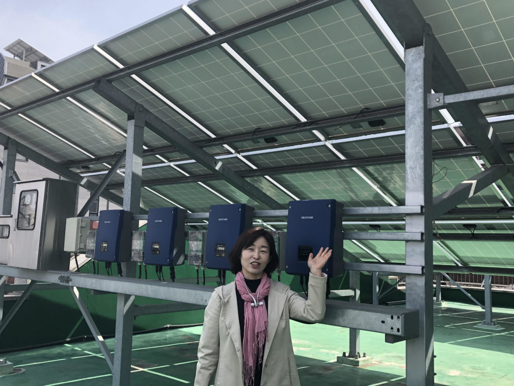 Eunsook Cho of Won Buddhist Eco Network stands in front of the solar panels on the roof of Song-cheon Won Buddhist temple in Seoul. (Sherry Simpson/GroundTruth)