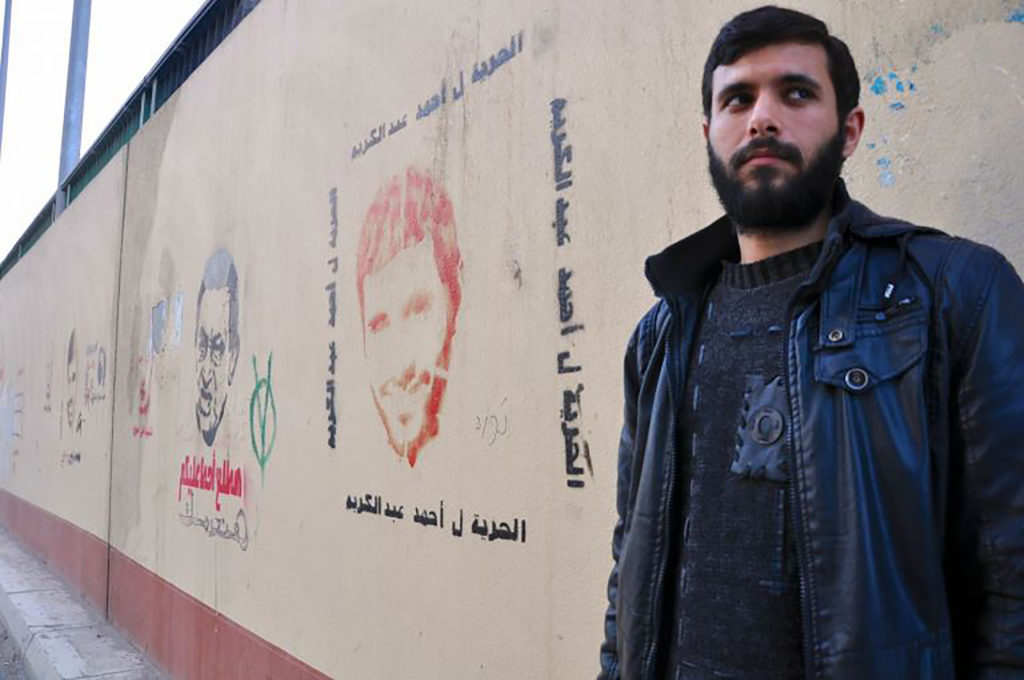 Ahmed in 2013, after he was released from prison for blogging anti-Mubarak critiques. He stands next to graffiti of his face, advocating for his freedom. (Lauren Bohn/GroundTruth)