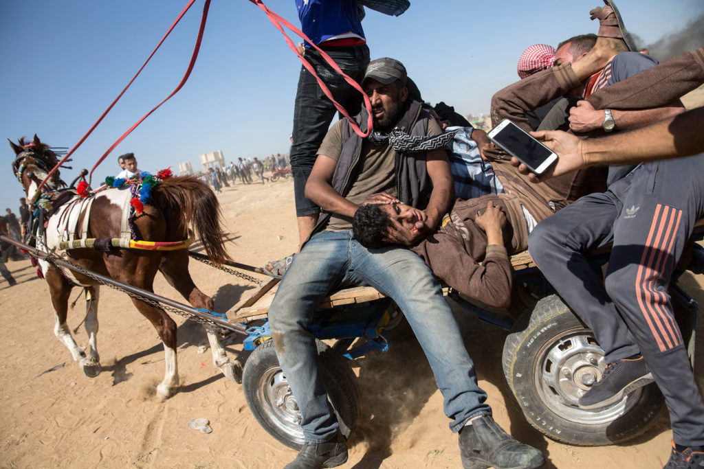 An injured Palestinian shot by Israeli forces is evacuated  by wagon and horse. (Heidi Levine/GroundTruth)