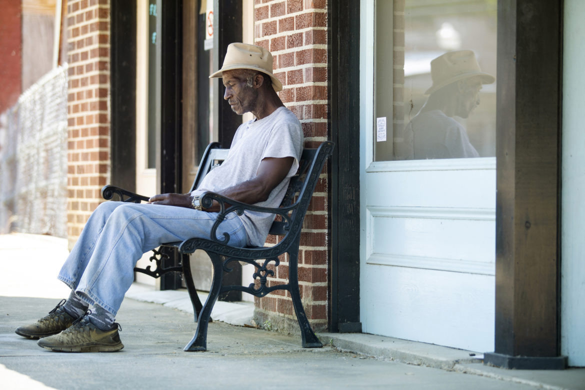 Life-long Utica resident Mack Sears, 68, sits on a bench in the 100 block of West Main Street after leaving Hope Credit Union in Utica Wednesday, June 6, 2018. Utica is about 83 percent African American. Nearly 28 percent of the population lives in poverty.