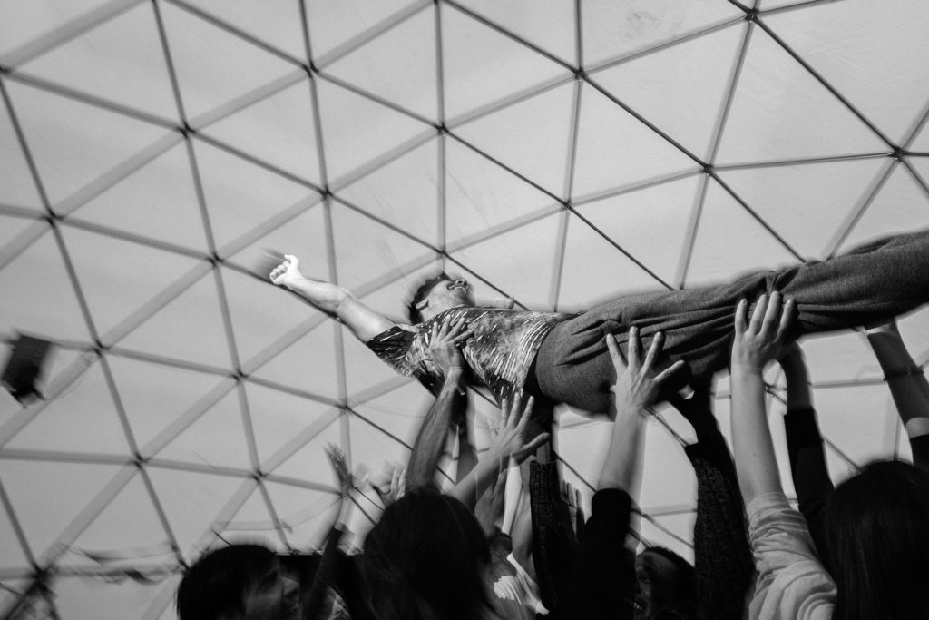 During a February 15 workshop in The Dome, people take turns doing group trust falls. One person teeters slightly and the group catches them, then falls slightly more, and then at last falls fully into the waiting hands of the others who lift them up and carry them around the space. (Photo by Annabelle Marcovici/GroundTruth)